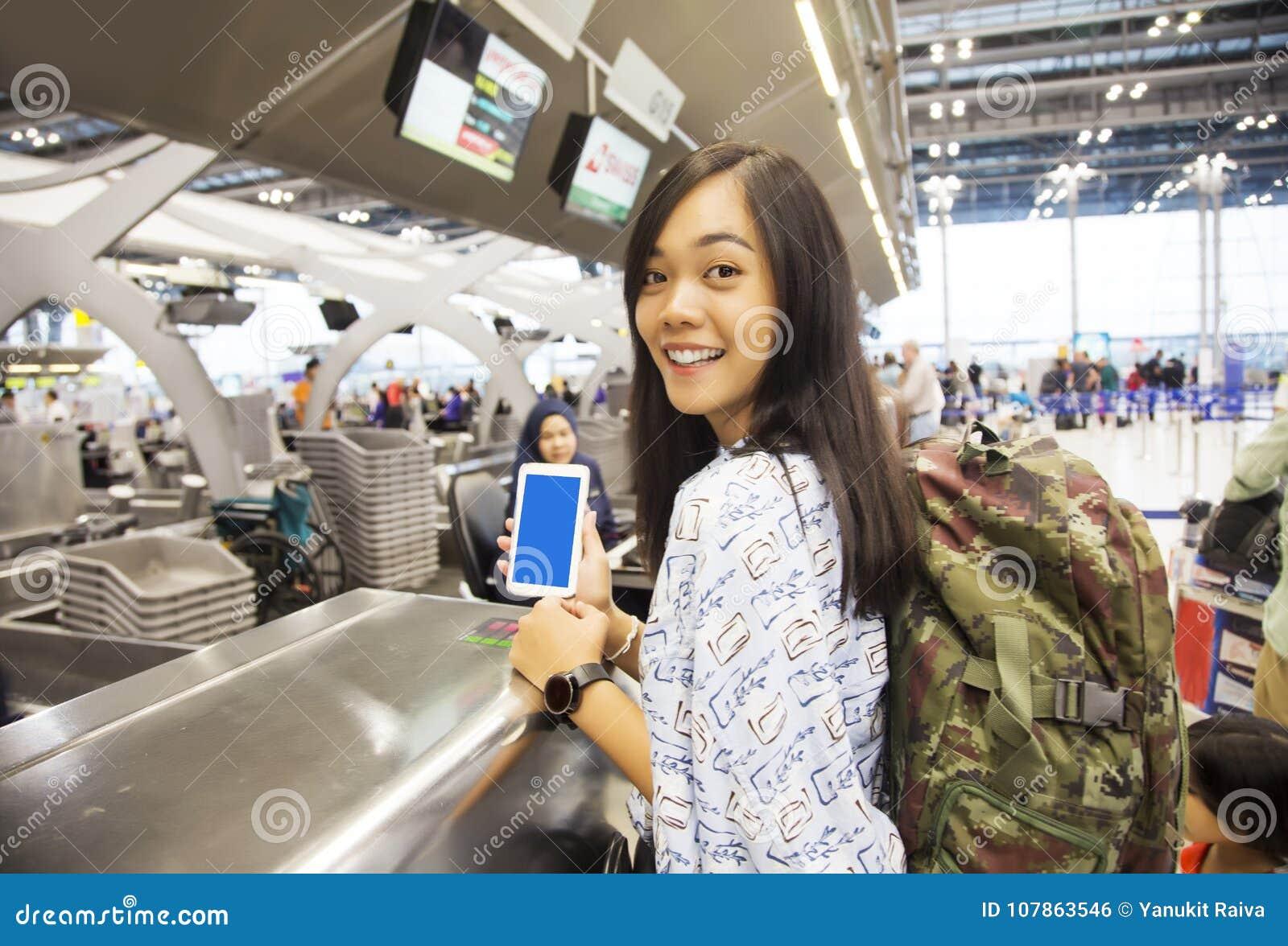 Asiatische Damenkontrolle im Flug mit ihrem Mobile