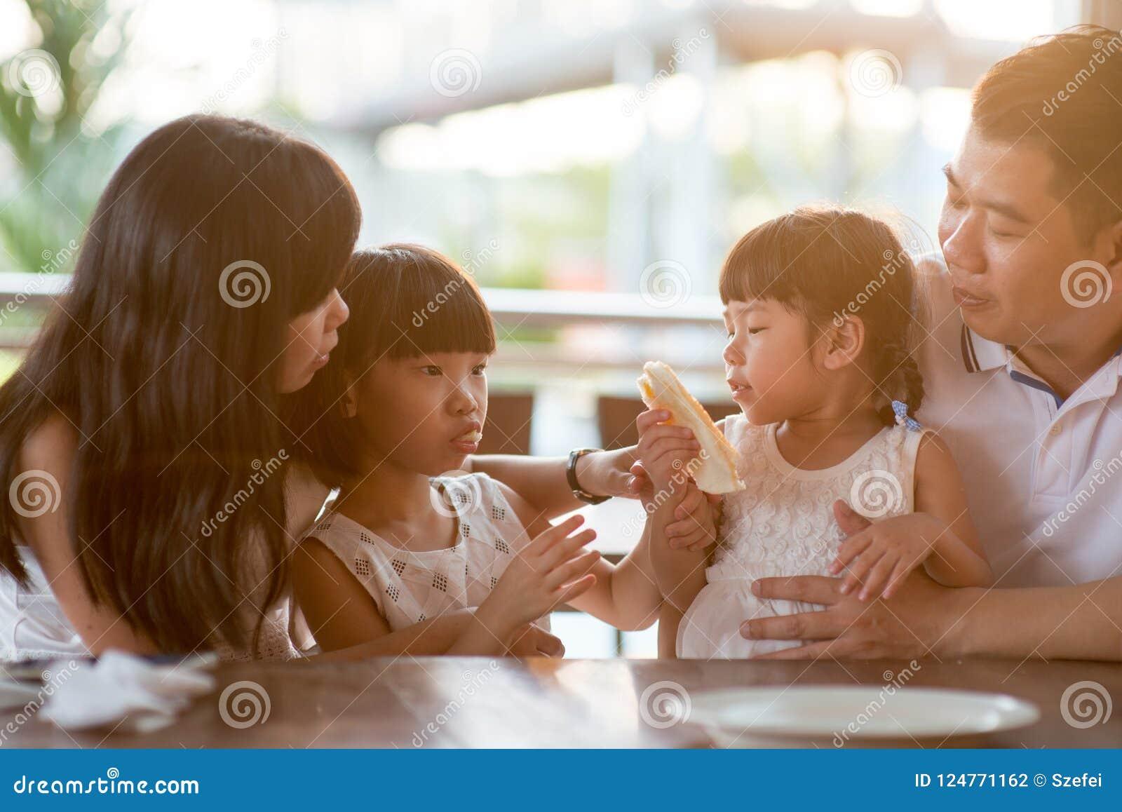 Asiatische Familie, die Lebensmittel am Café isst