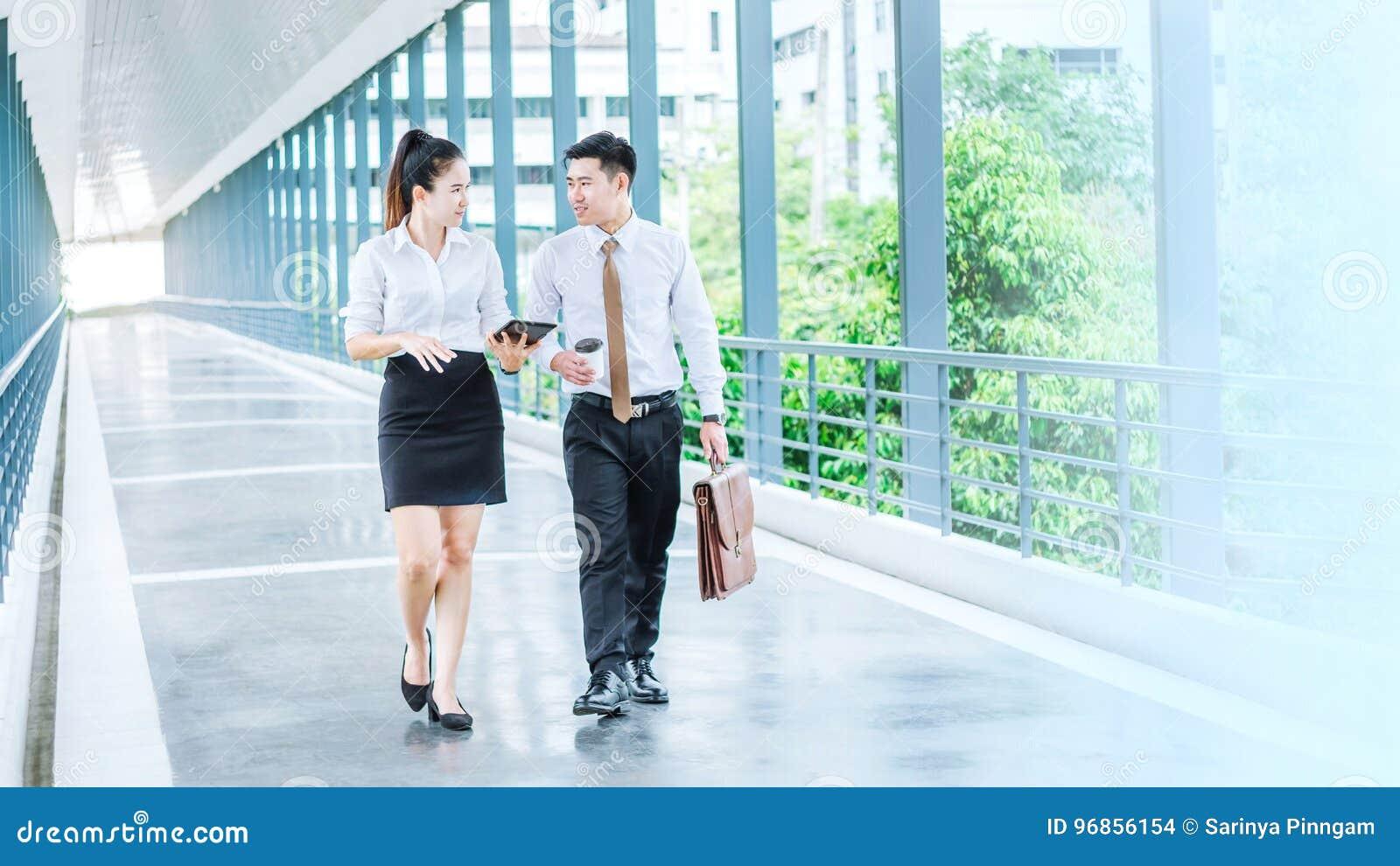 Asiatische Geschäftsleute, die draußen über Arbeit von gehen und sprechen