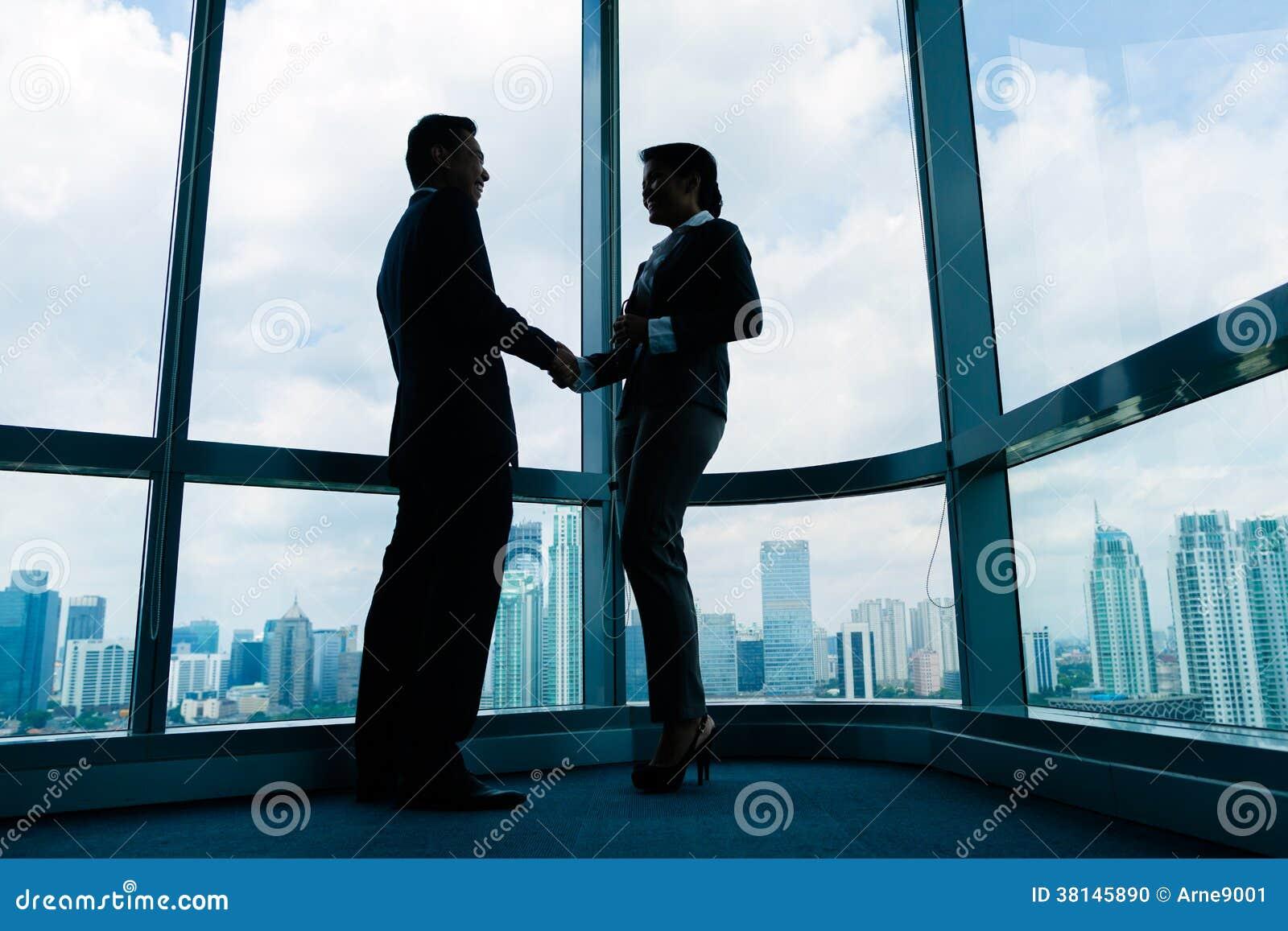 Asiatische Geschäftsleute, die Hände rütteln