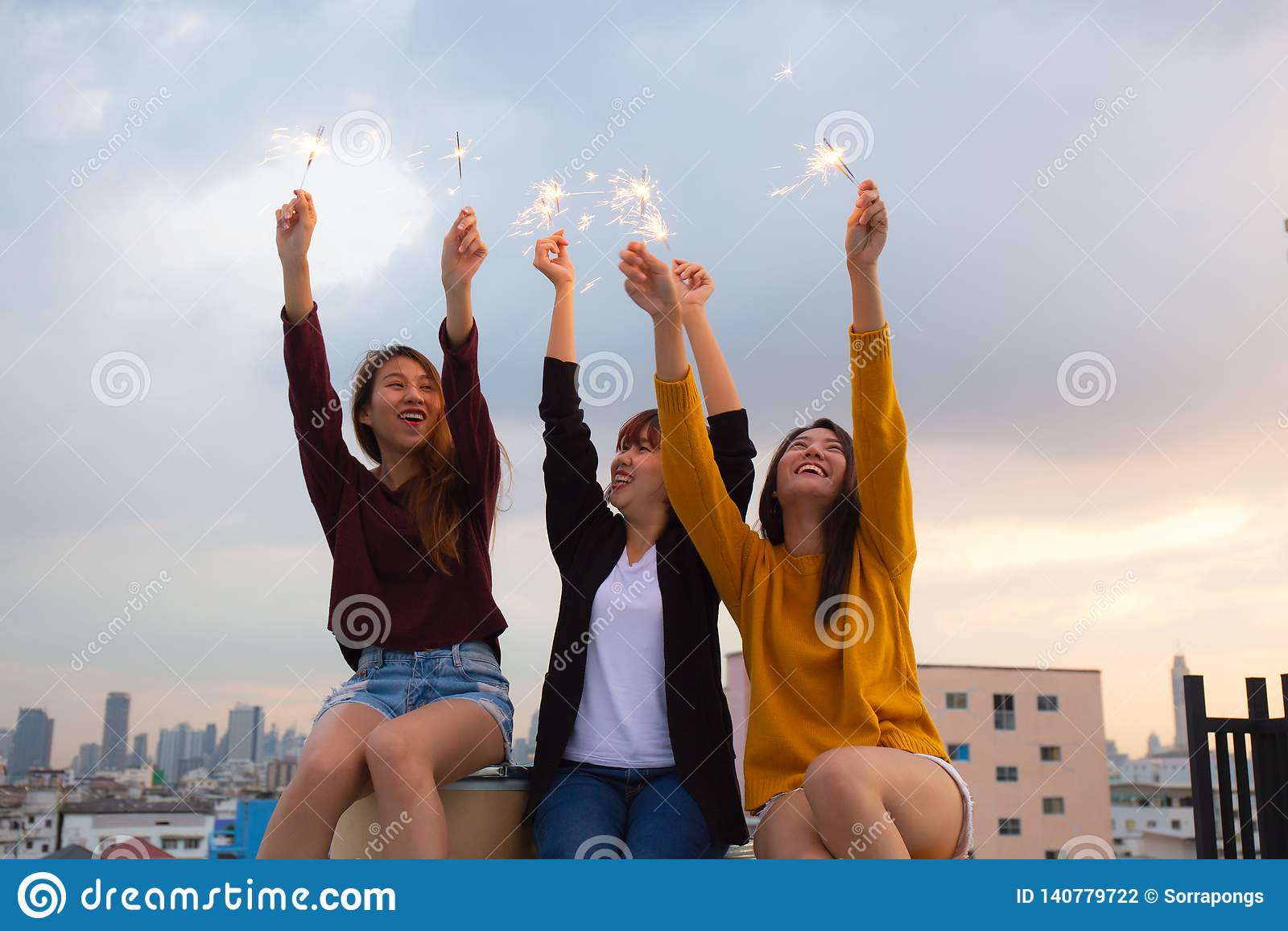 Asiatische Gruppe Freunde, die Wunderkerzen beleuchten und Freiheit bei Sonnenuntergang, asiatische Frau glücklich hält Wunderker