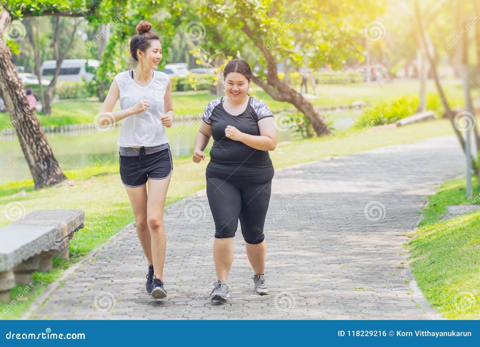 Asiatische jugendlich laufende fette und dünne rüttelnde Freundschaft