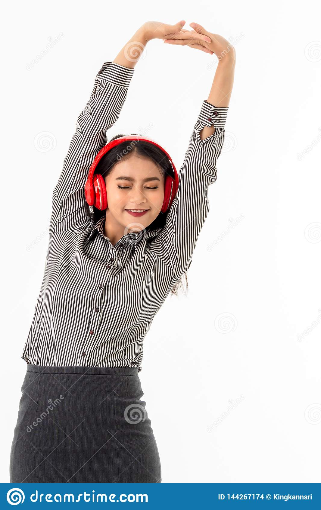 Asiatische junge Dame, welche die roten Kopfhörer ausdehnen ihre Arme über ihrem Kopf trägt