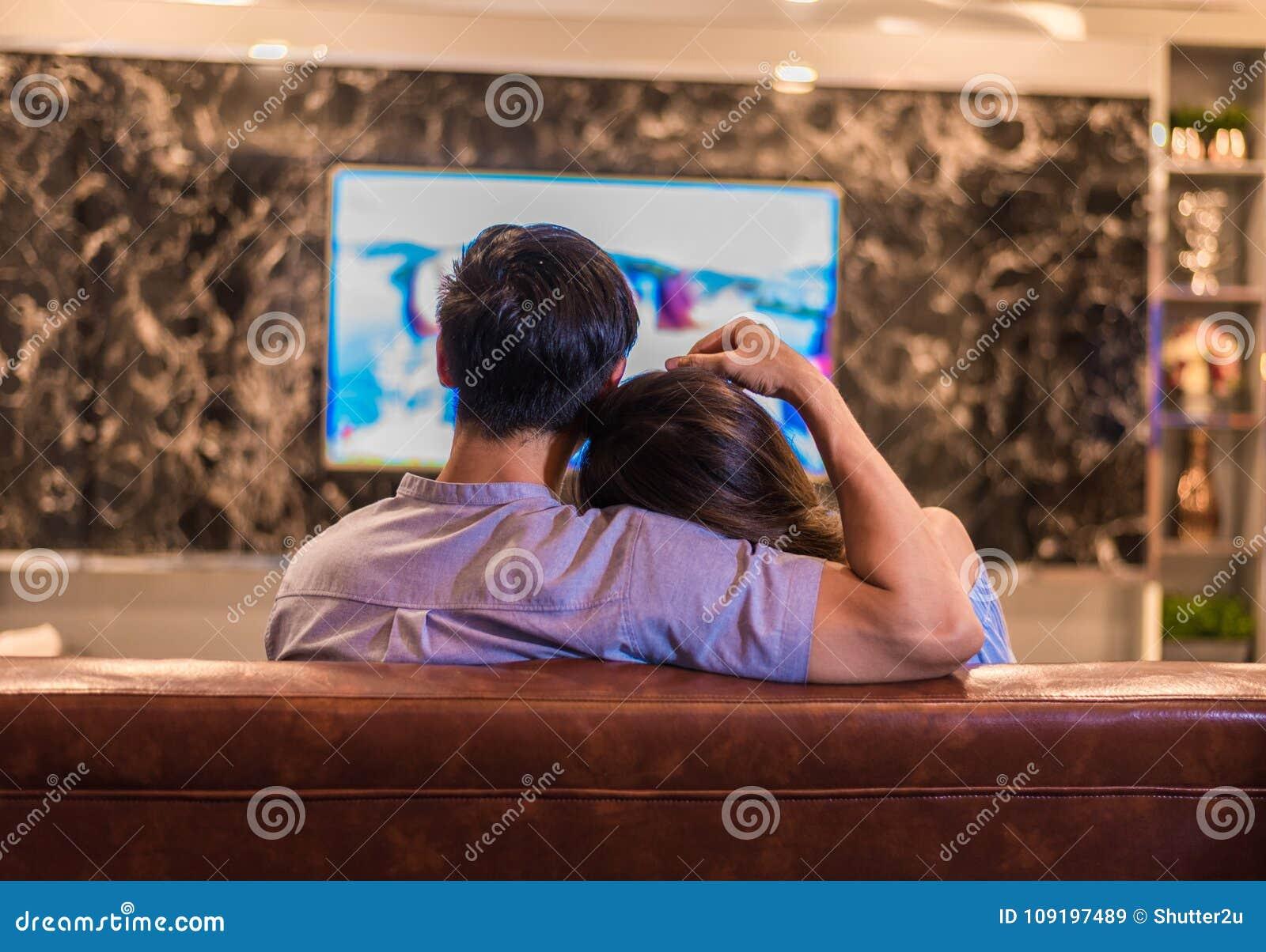 Asiatische junge Liebhaber, die auf Sofa fernsehen Paare und wirkliches