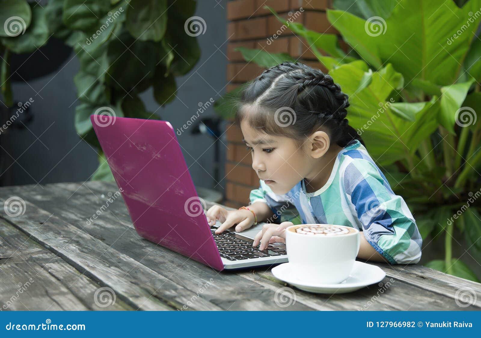 Asiatische Kinder unter Verwendung des Laptops und der Kaffeetasse auf hölzerner Tabelle