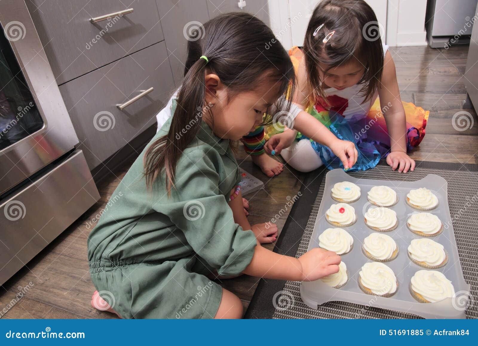 Asiatische Kleinkinder Die Kleine Kuchen In Der Kuche Verzieren