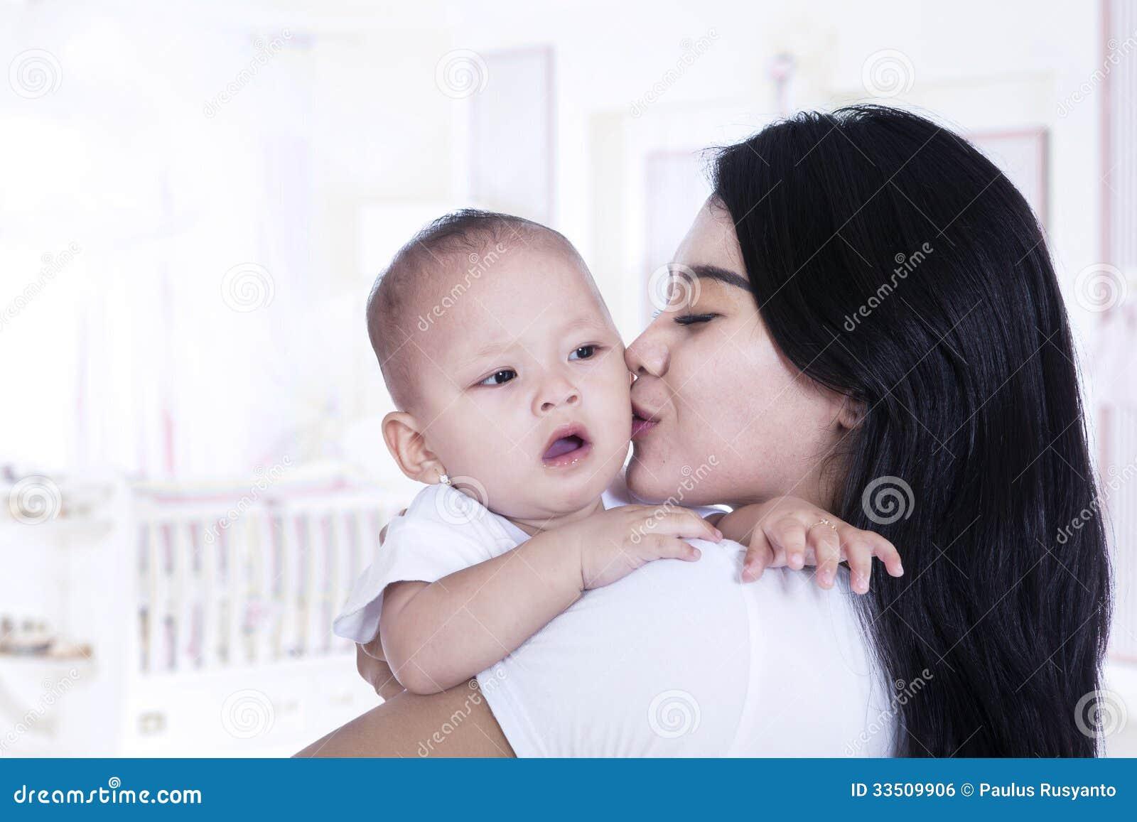 Asiatische Mutter, die zu Hause ihr Baby küsst
