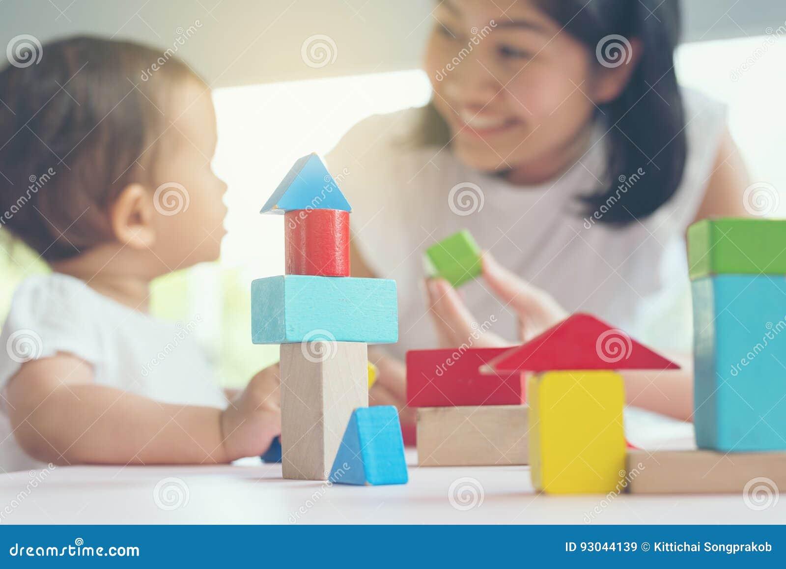 Asiatische Mutter und Mädchen scherzen das Spielen mit Blöcken Selektiver Fokus und