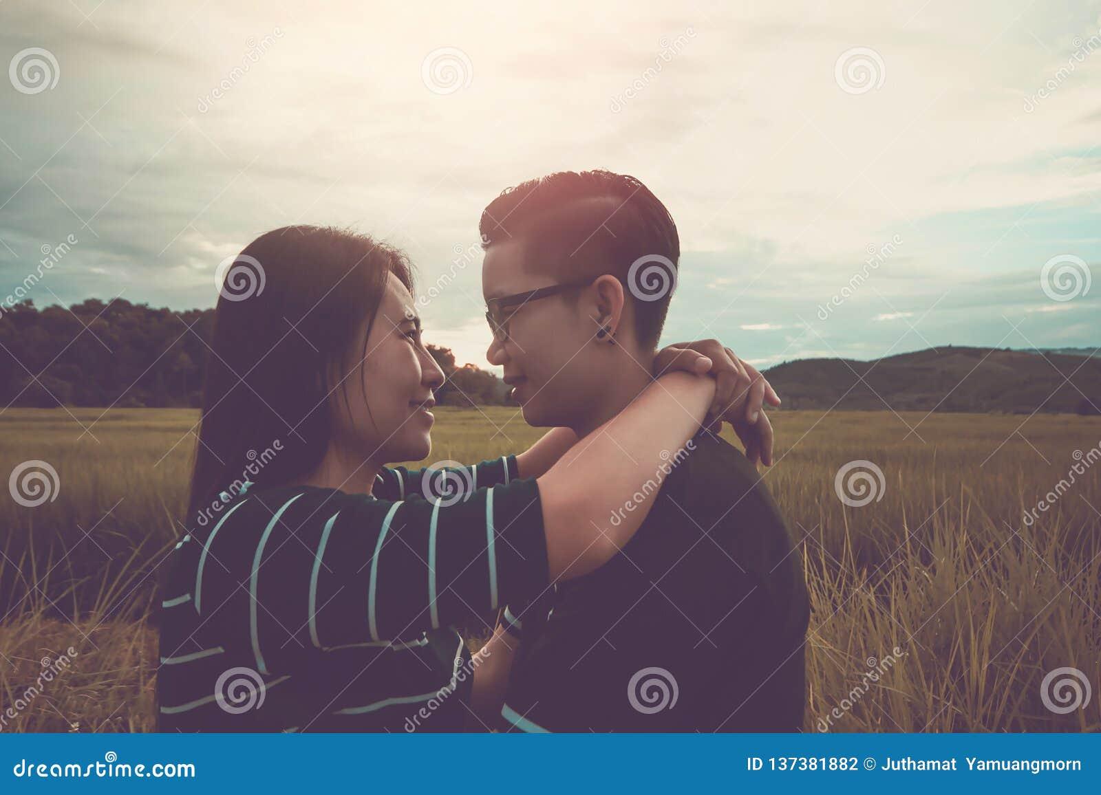 Asiatische, romantische Paare oder Homosexualität, weibliche Liebesumarmung auf dem Reisfeld mit Sonnenuntergang, Valentinstaglie