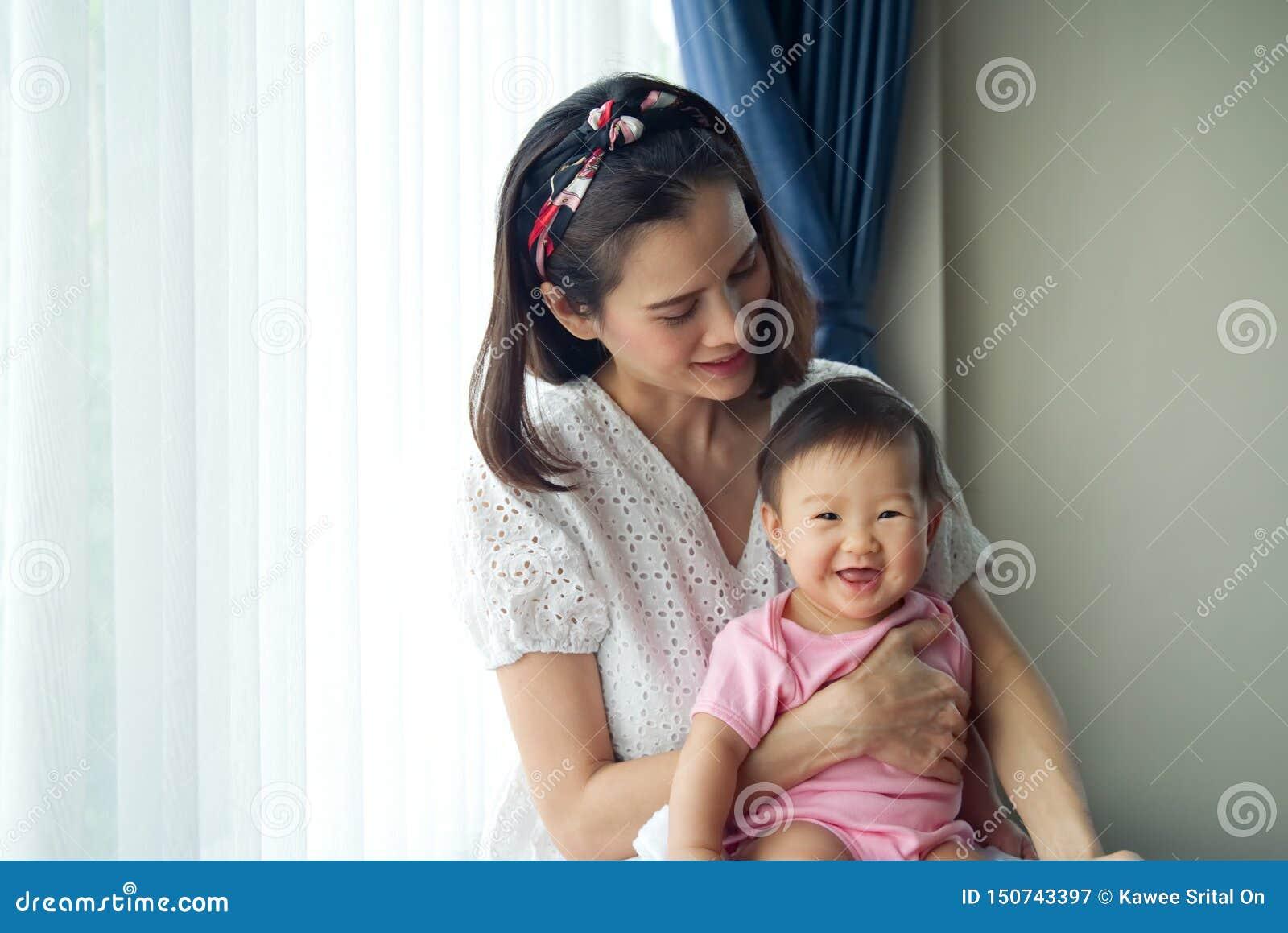 Asiatische schöne Mutter, die ihr nettes Baby in ihren Armen zu Hause sitzen nahe dem Fenster hält