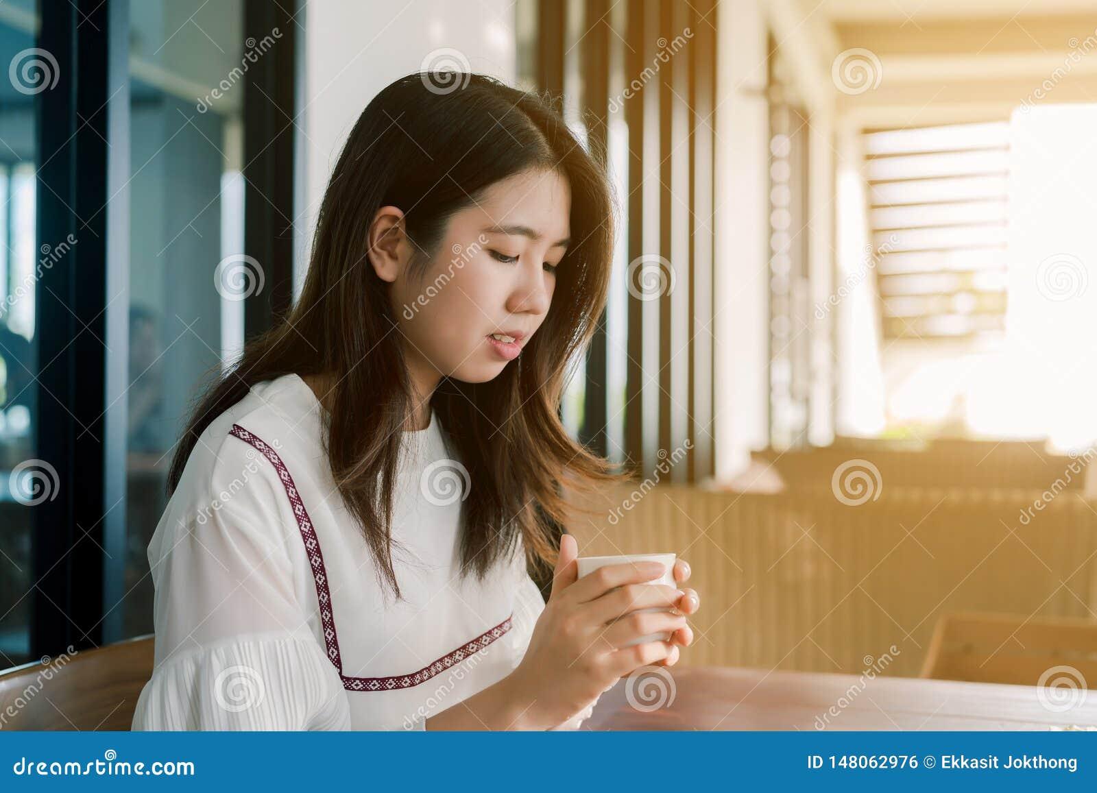 Asiatische Sch?nheit, die gl?cklich ein wei?es Hemd, Sitzen, trinkender hei?er Kaffee in der B?ckerei hell morgens tr?gt