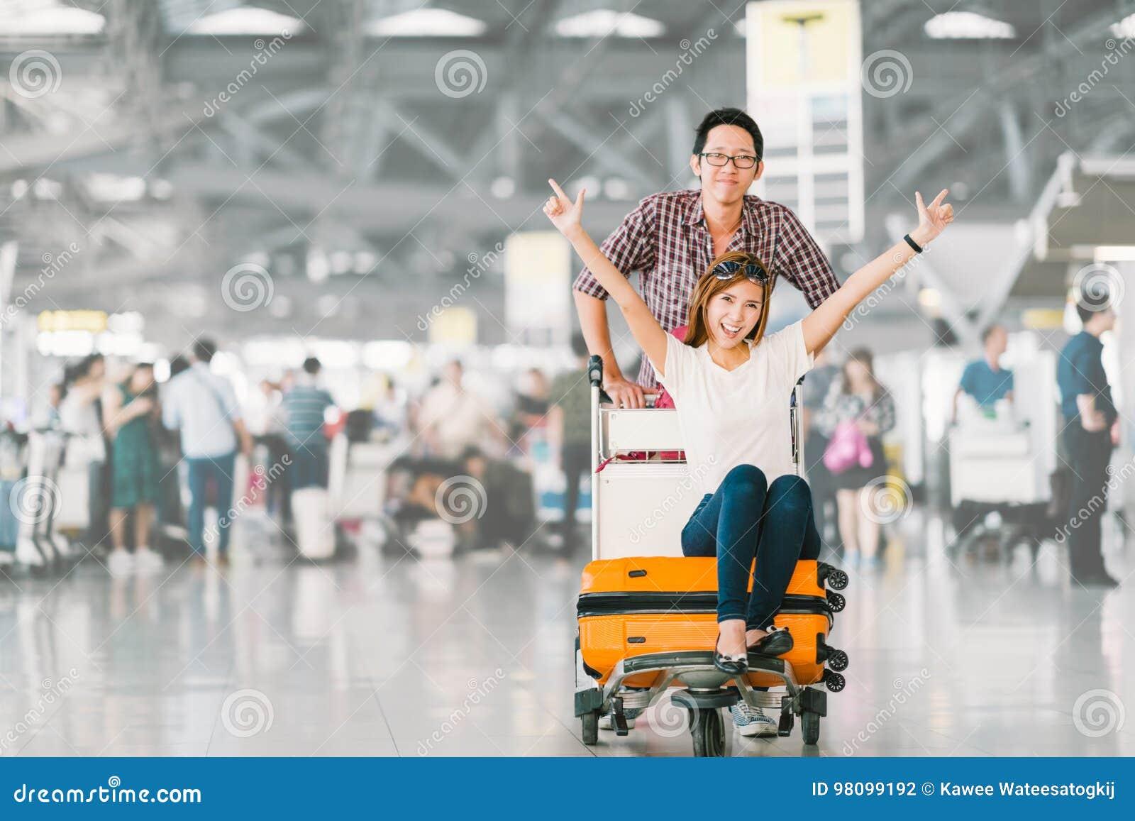 Asiatische touristische Paare glücklich und zusammen für die Reise, Freundin aufgeregt, die auf Kofferkuli oder Gepäckwarenkorb s