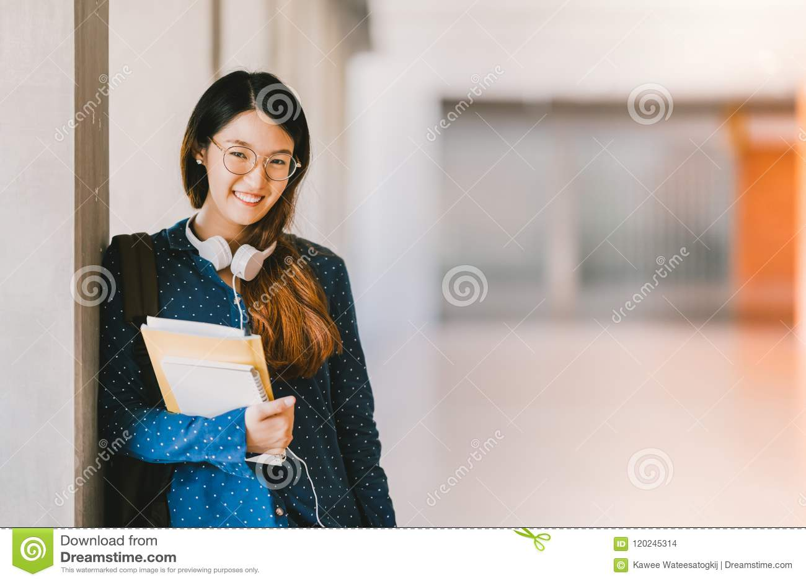 Asiatische tragende Brillen der Oberschülerin oder des Studenten, lächelnd im Universitätsgelände mit Kopienraum getrennte alte B