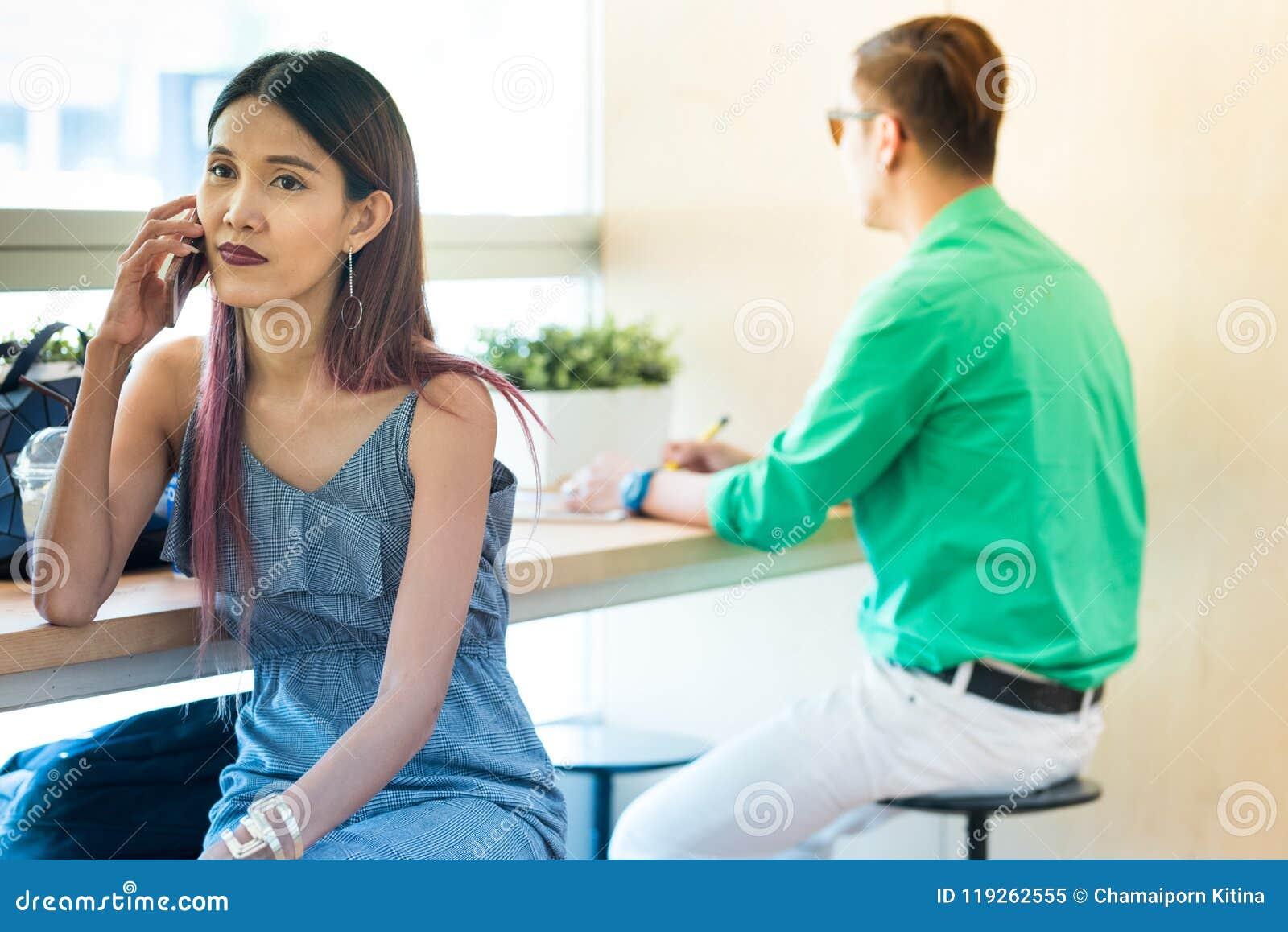 Asiatischer Damengebrauch und -gespräch im intelligenten Handy beim Sitzen in c