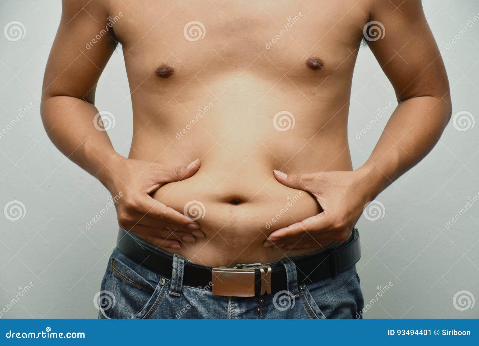 Asiatischer dicker Mann hat Cholesterin Er zeigt überschüssiges Fett des Bauches