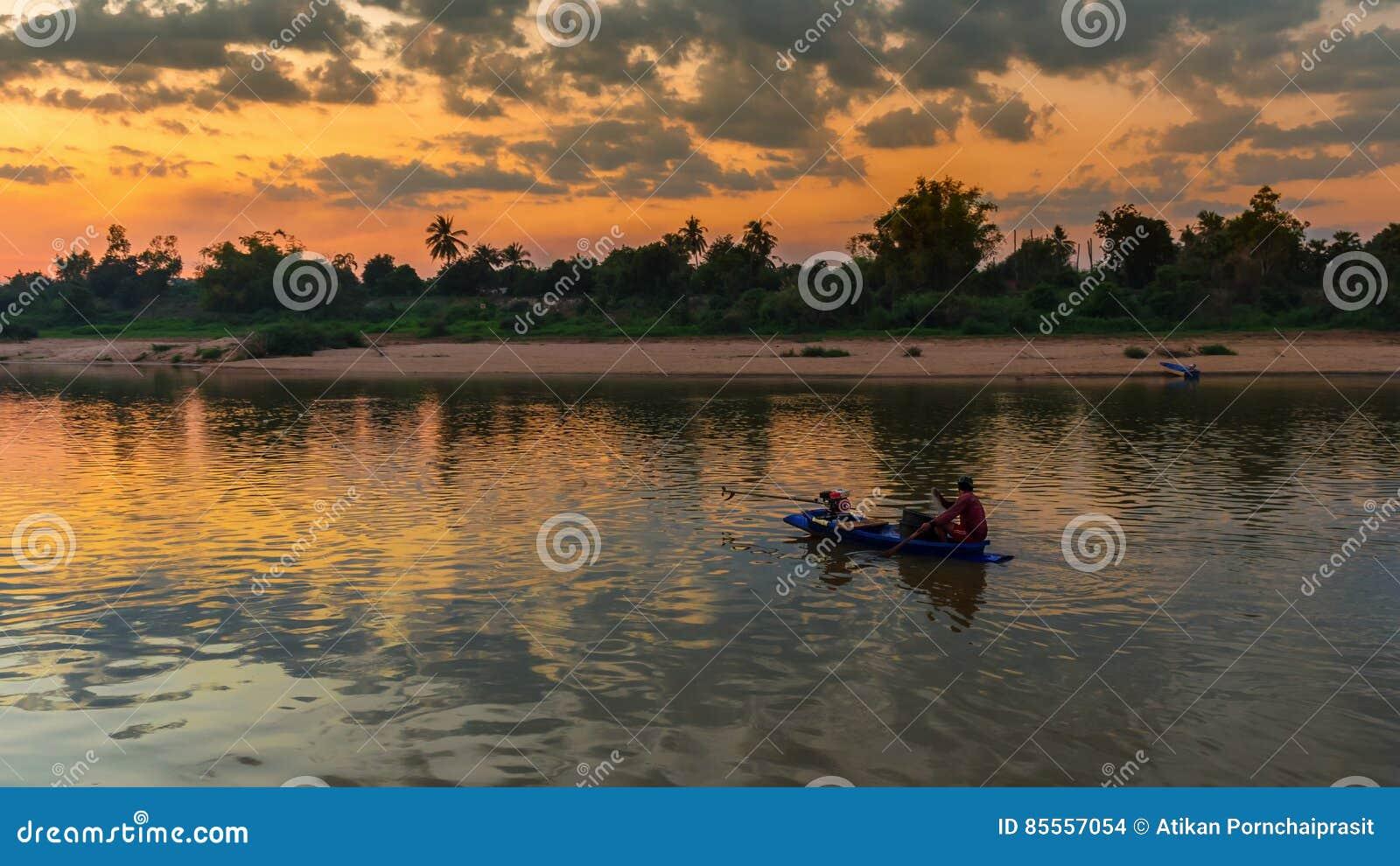 Asiatischer Fischer auf dem hölzernen Boot, das ein Netz für anziehendes freshw wirft