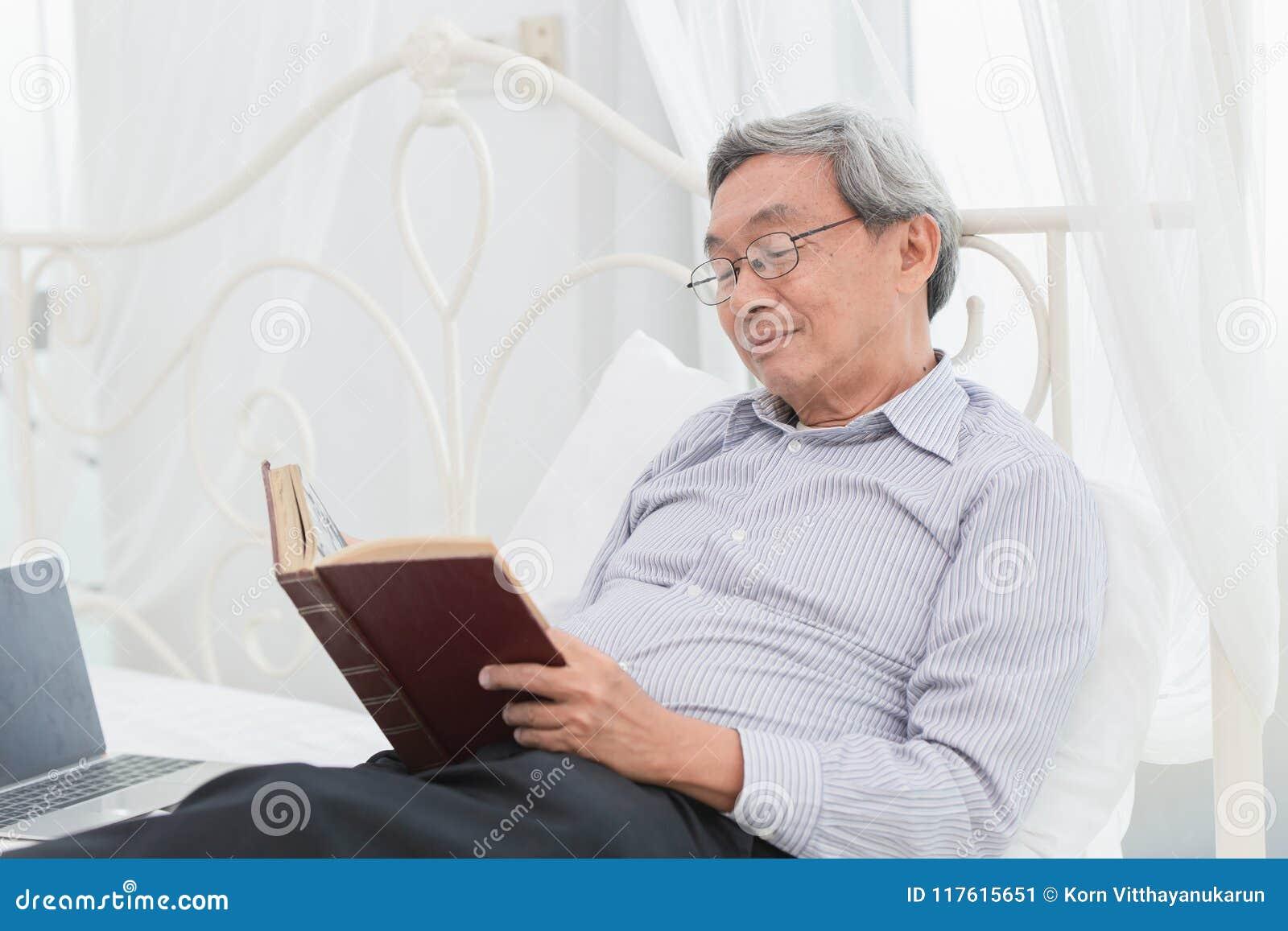Asiatischer Glasprofessor des alten Mannes genießen, Lehrbuch zu lesen