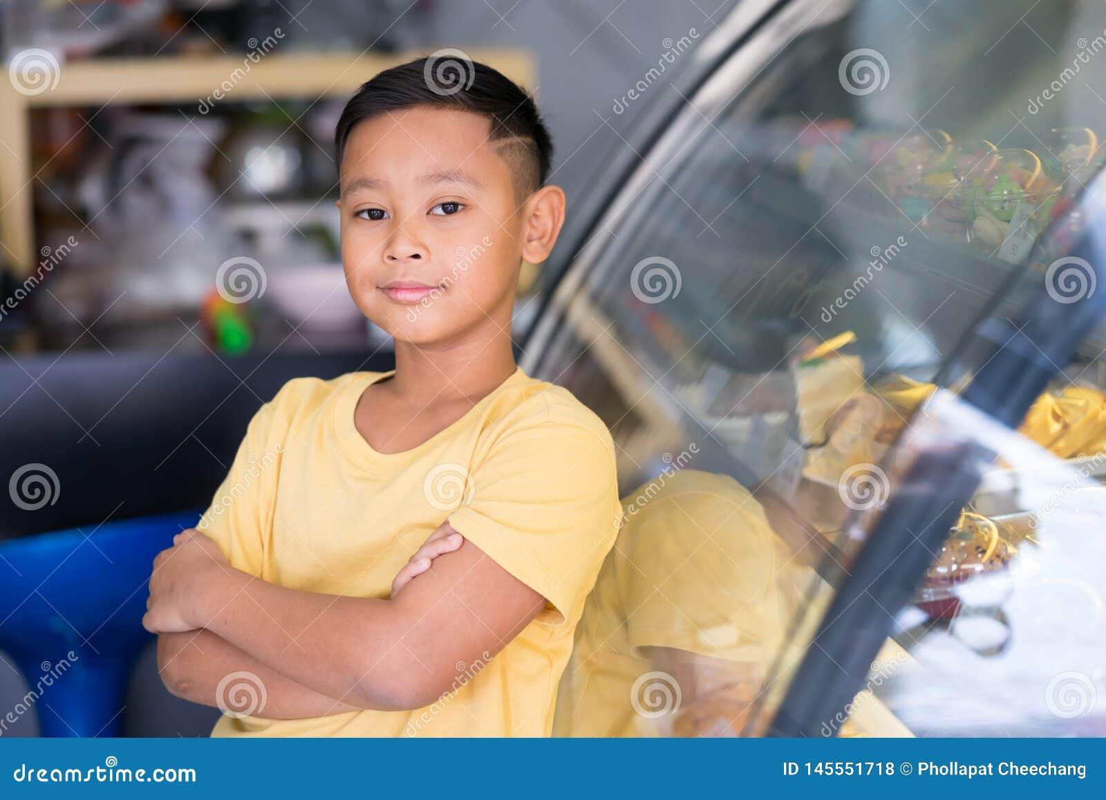 Asiatischer Kinderjunge, der am B?ckereigesch?ft wartet und B?ckerei die er beschlie?t zu m?gen