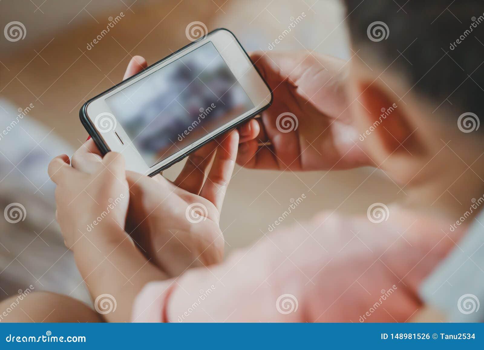 Asiatischer Kinderjungenholding- und -touch Screen von Smartphone