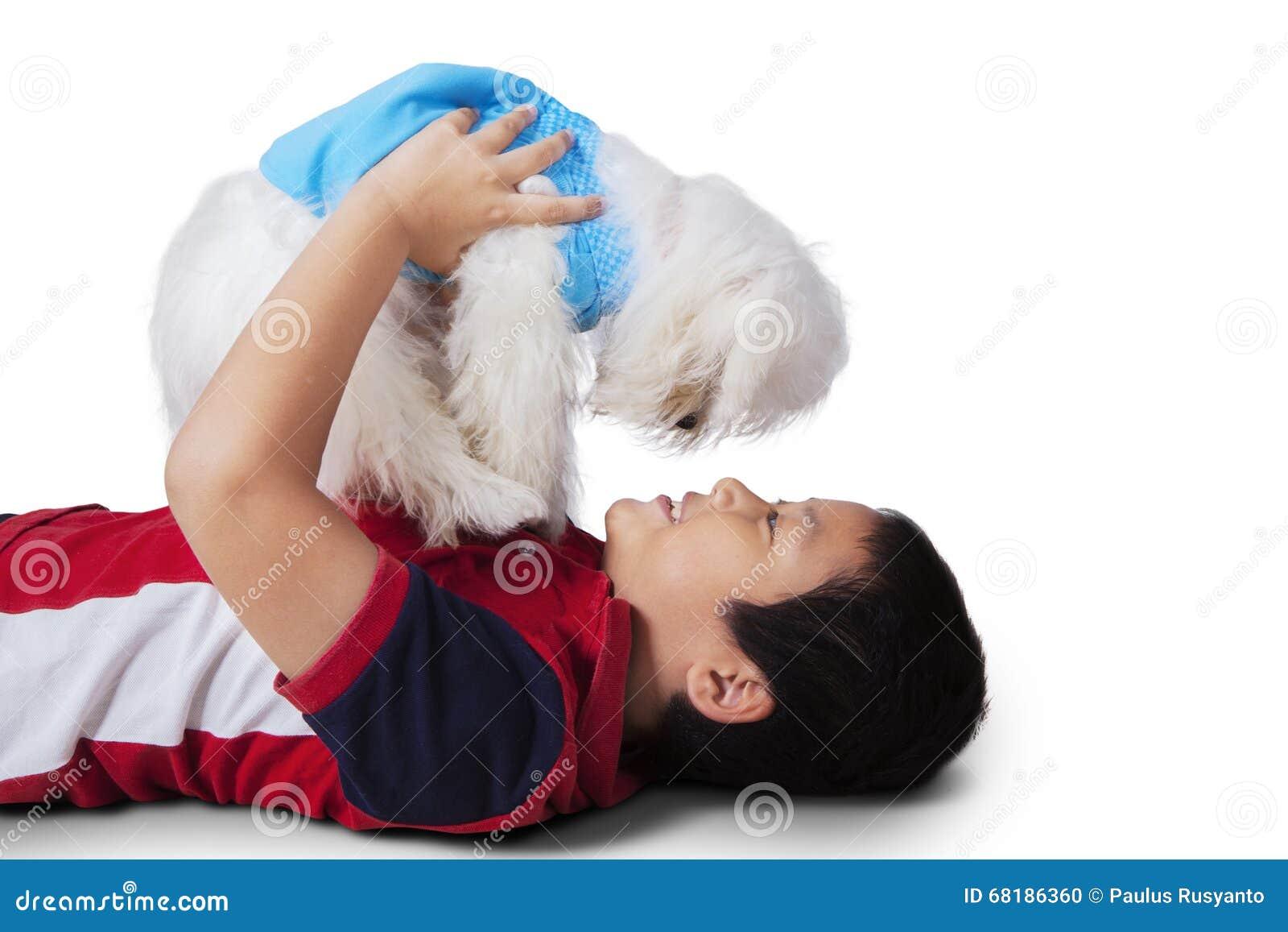 Asiatischer kleiner Junge, der maltesischen Hund spielt