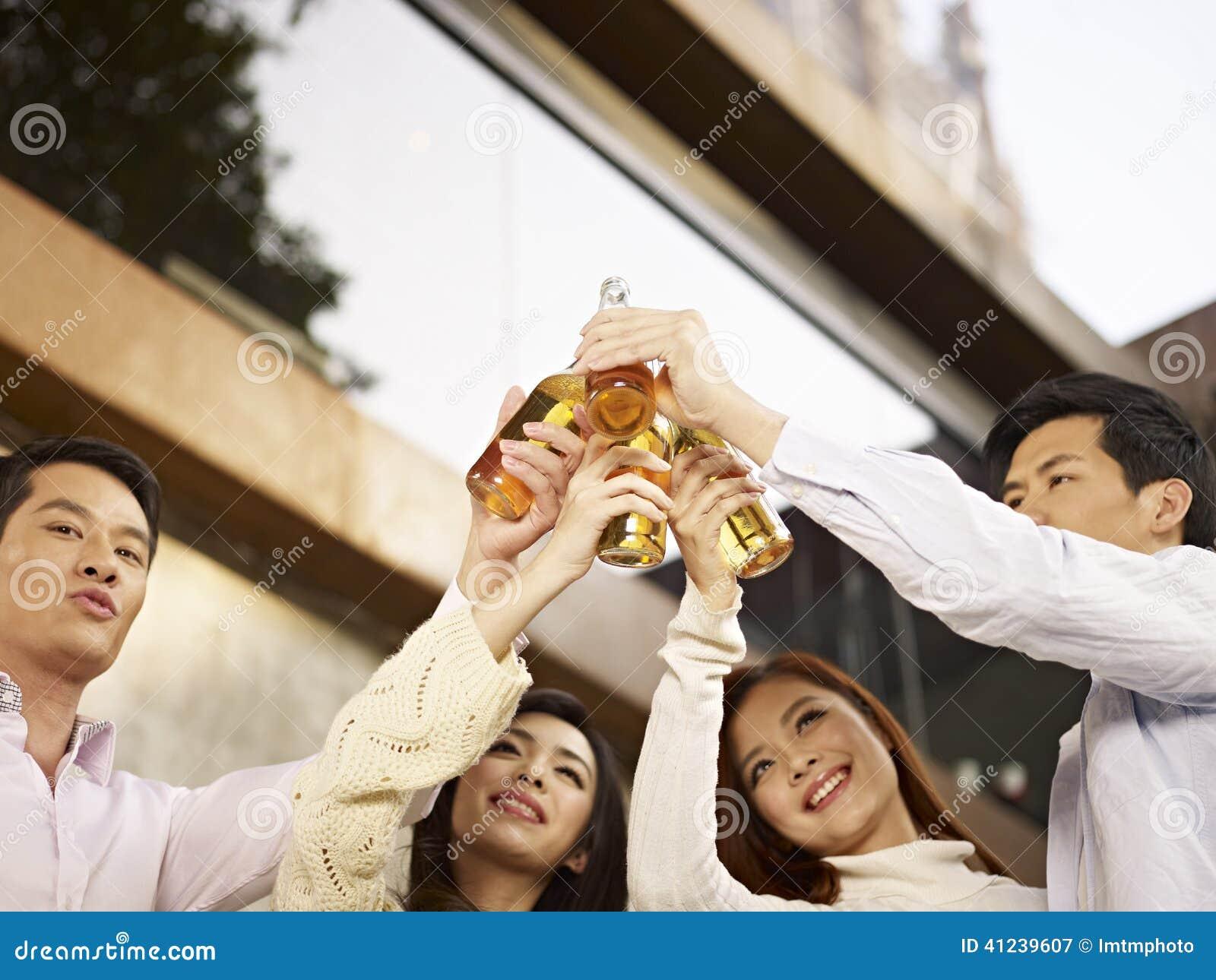 Asiatischer Knabe, der mit Bier feiert