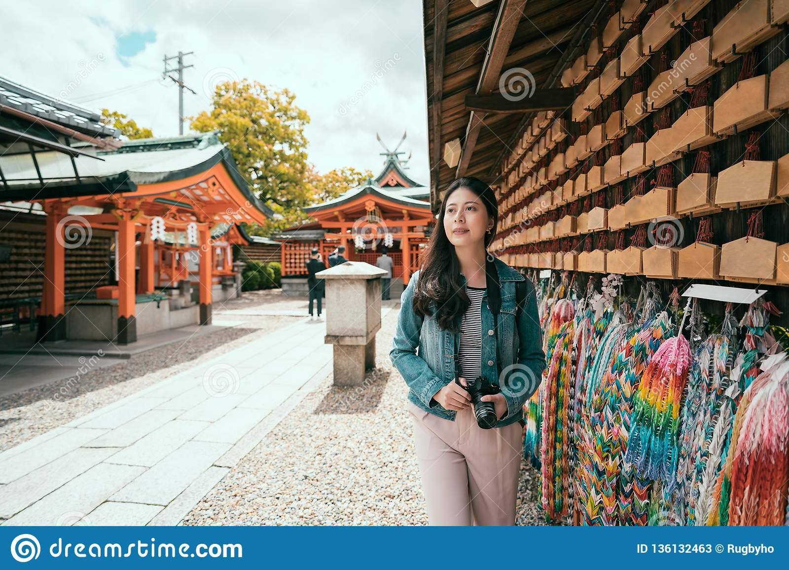 Asiatischer Mädchenreisender, der entlang betende Wand geht