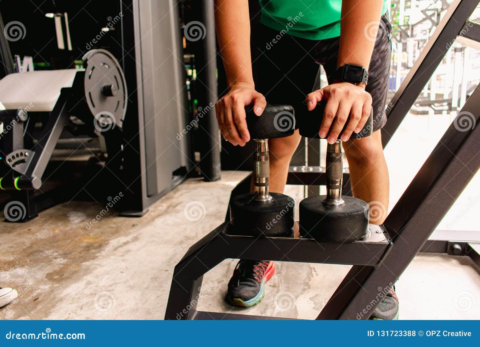 Asiatischer Mann Bodybuilder mit Dummkopfgewichten treiben hübsche athletische Übungen an Metapher-Eignung und Trainingskonzeptüb