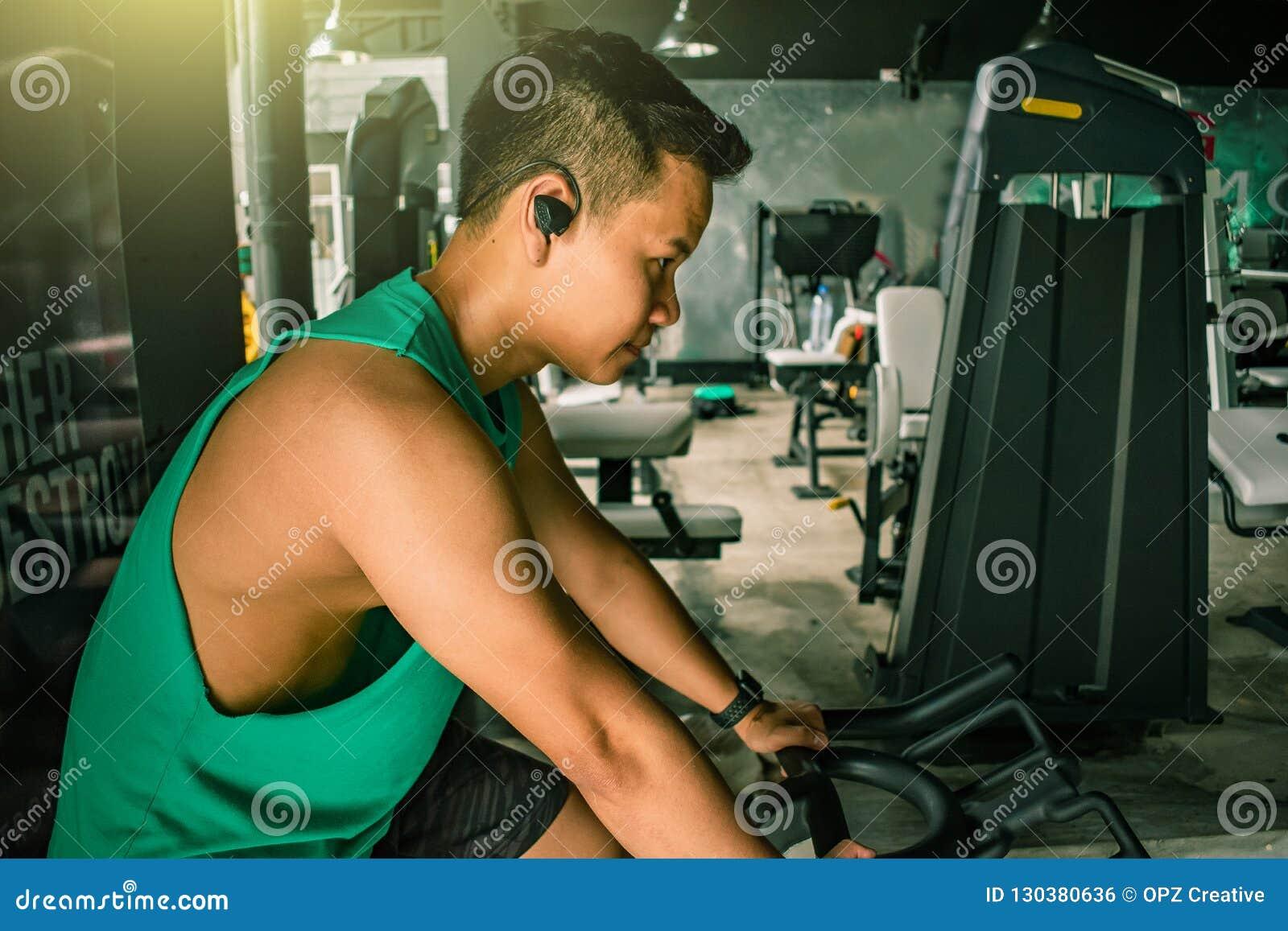 Asiatischer Mann Bodybuilder mit Fahrradmaschine belastet Energie handsom