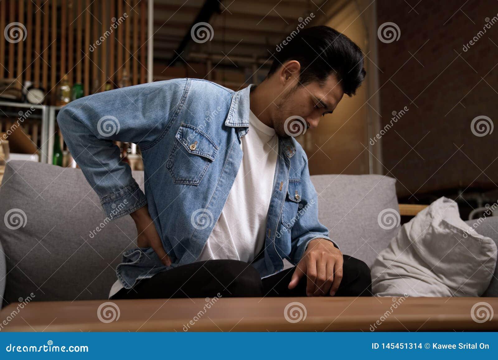 Asiatischer Mann, der auf dem Sofa hat Rückenschmerzen und zurück hält seins zu Hause sitzt