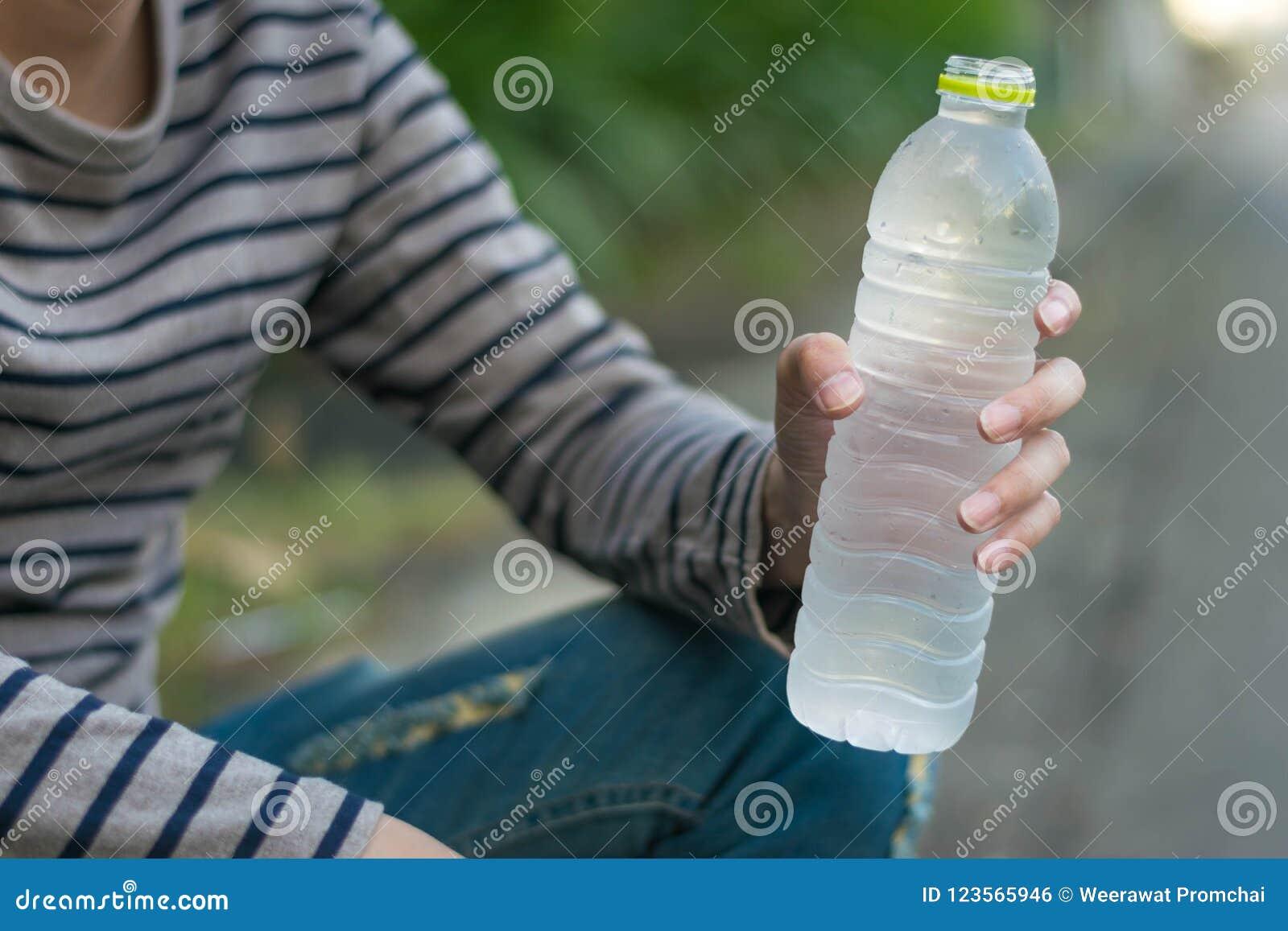 Asiatischer Mann, der Flasche Wasser sitzt und hält