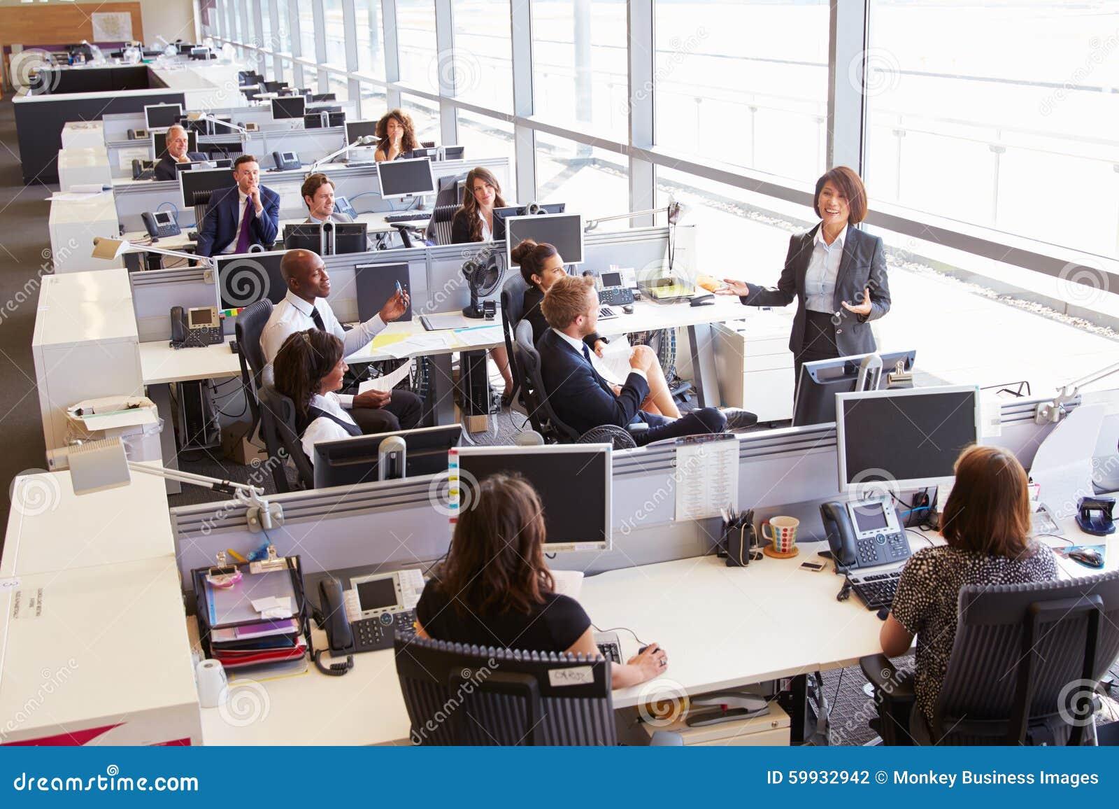 Asiatischer weiblicher Manager, welche zu Arbeitskräften im Bürogroßraum spricht