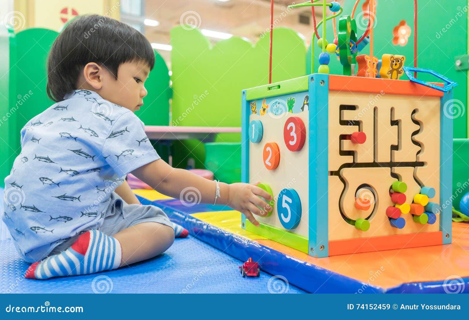 Asiatisches Baby, das mit pädagogischem Spielzeug spielt