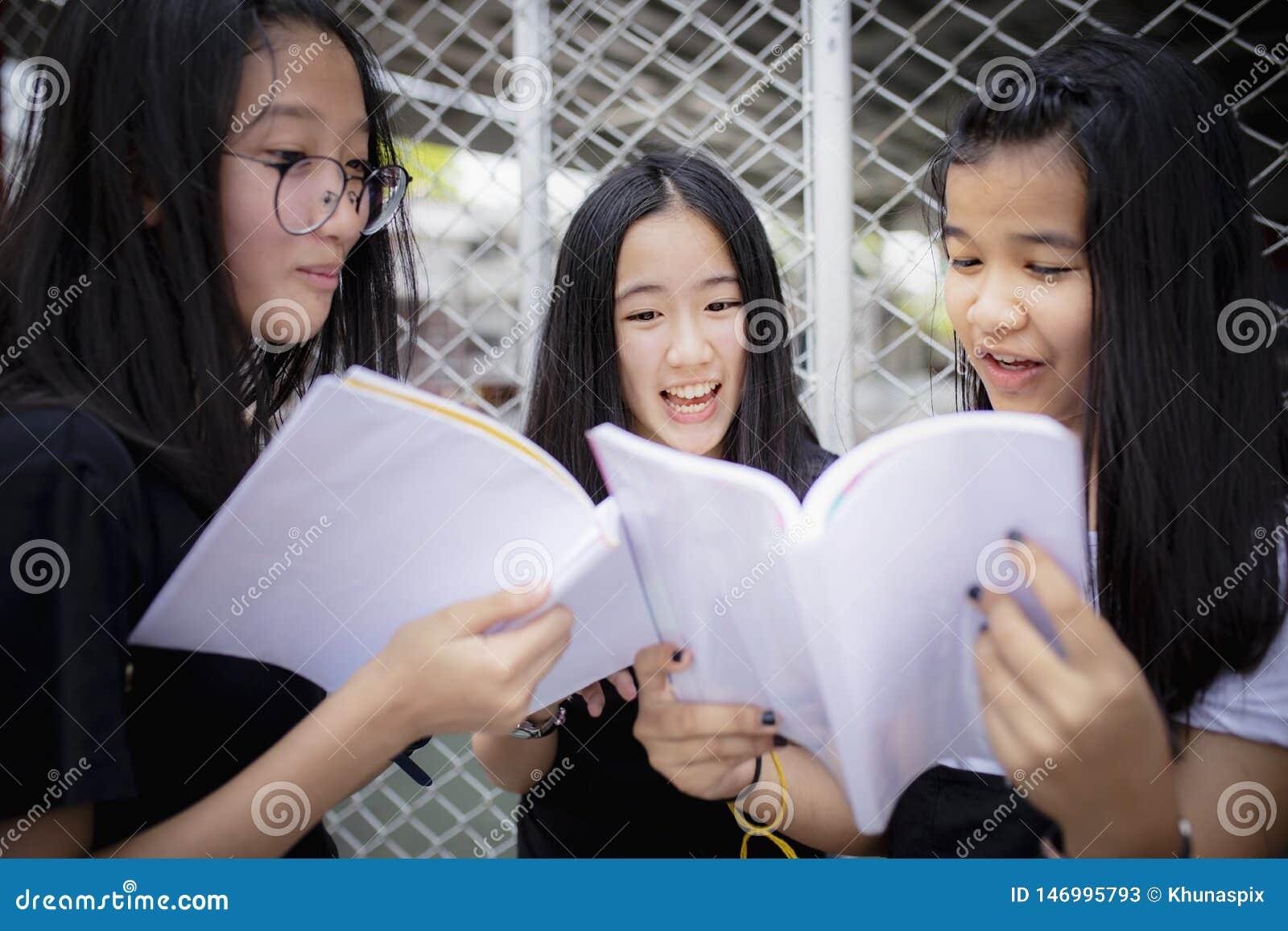 Asiatisches Jugendlichholdingschulbuch und Lachen mit dem Gl?ckgef?hl, das im Freien steht
