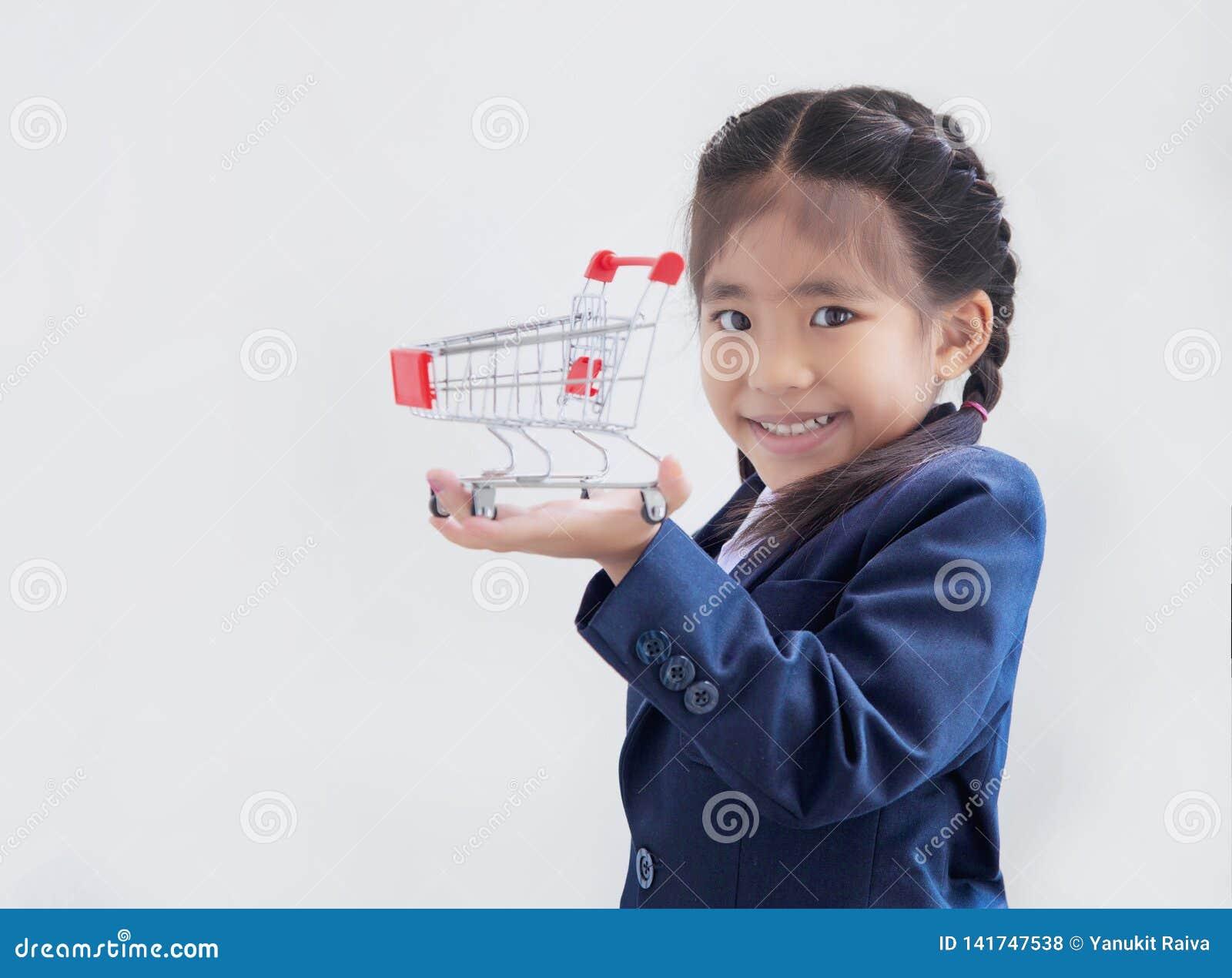 Asiatisches Kind mit dem Einkaufswagen, zum von prodcut darzustellen