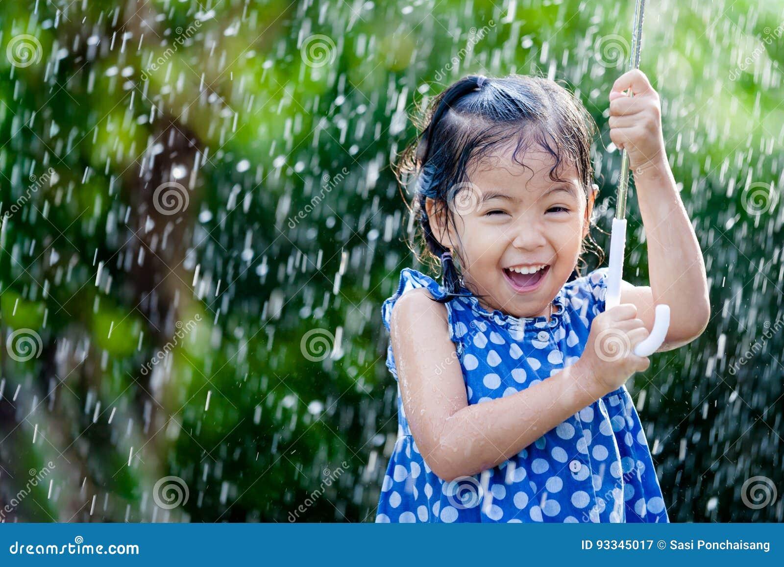 Asiatisches kleines Mädchen mit Regenschirm im Regen
