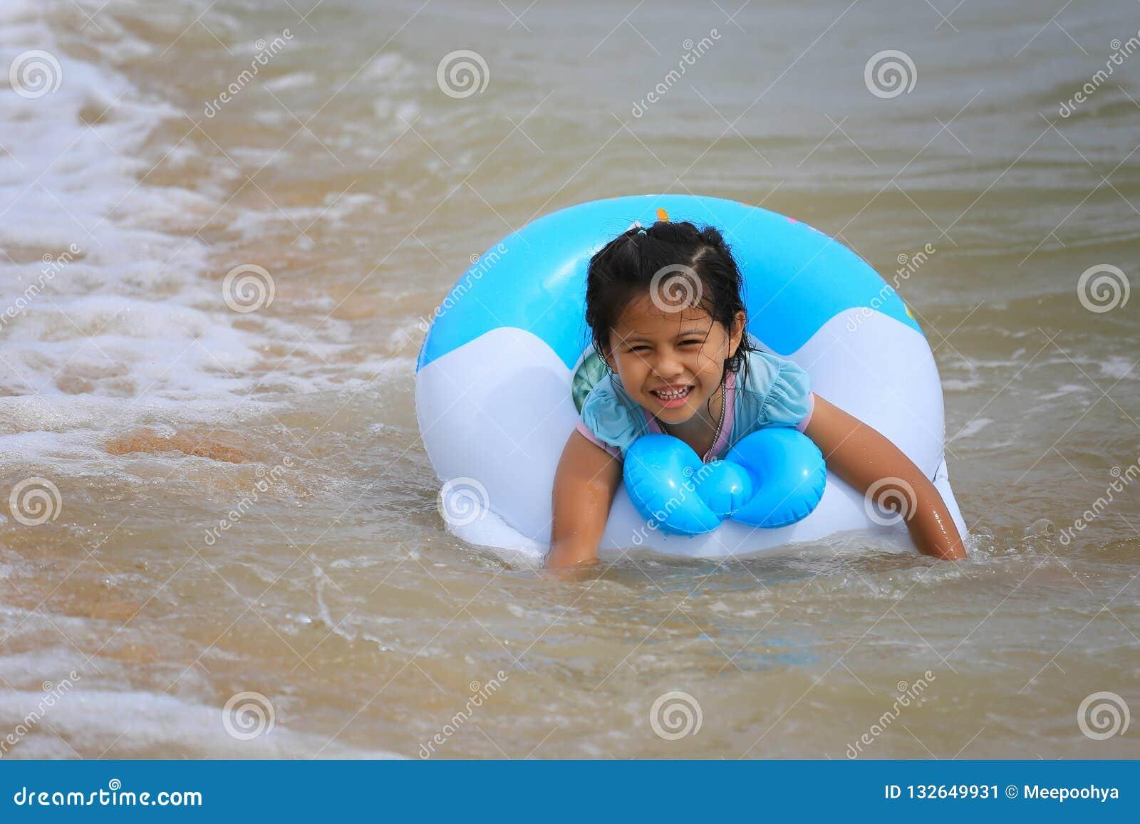 Asiatisches Mädchen in der Schwimmen an der Küste mit einem Lächeln auf glücklichem