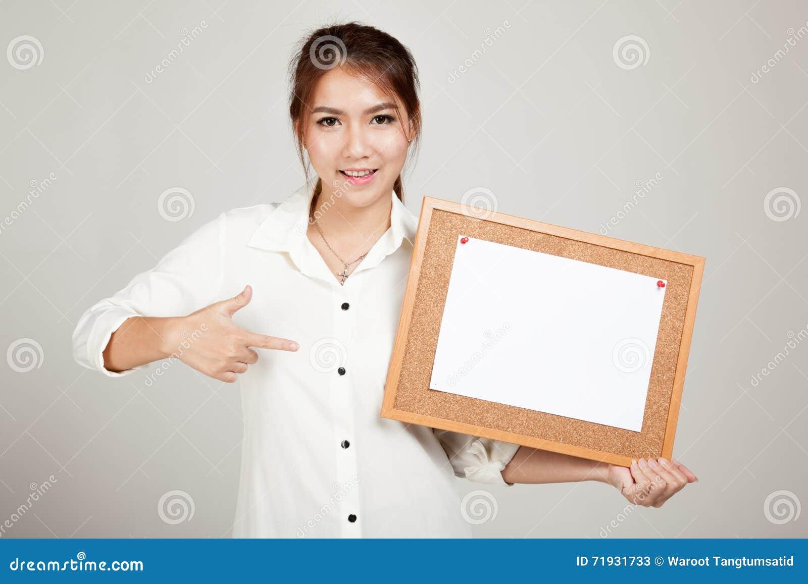 Asiatisches Mädchen mit Stift des leeren Papiers vom Korkenbrett