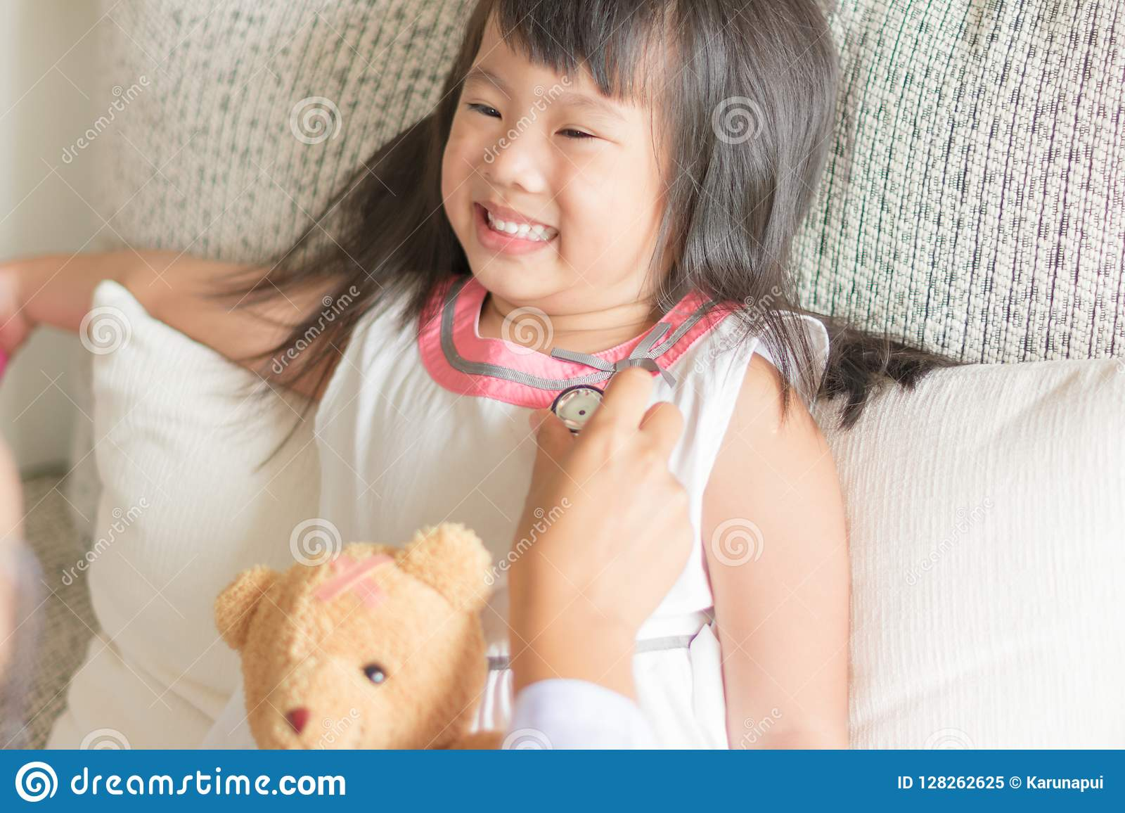 Asiatisches nettes kleines Mädchen ist lächelnd spielend und Doktor mit stetho