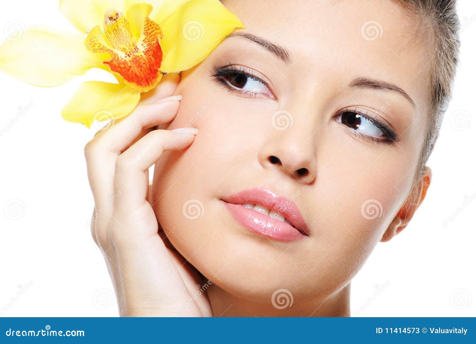 Asiatisches weibliches gesicht der attraktiven schönheit mit blume