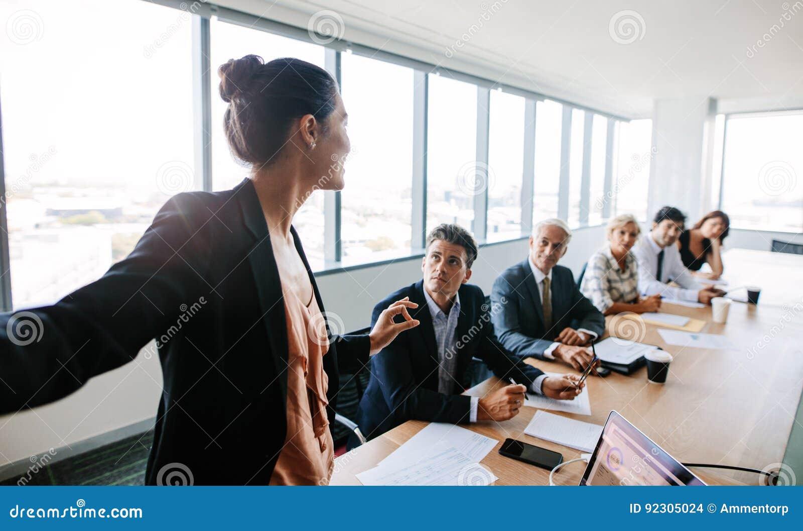 Asiatisk affärskvinna som ger presentation till coworkers