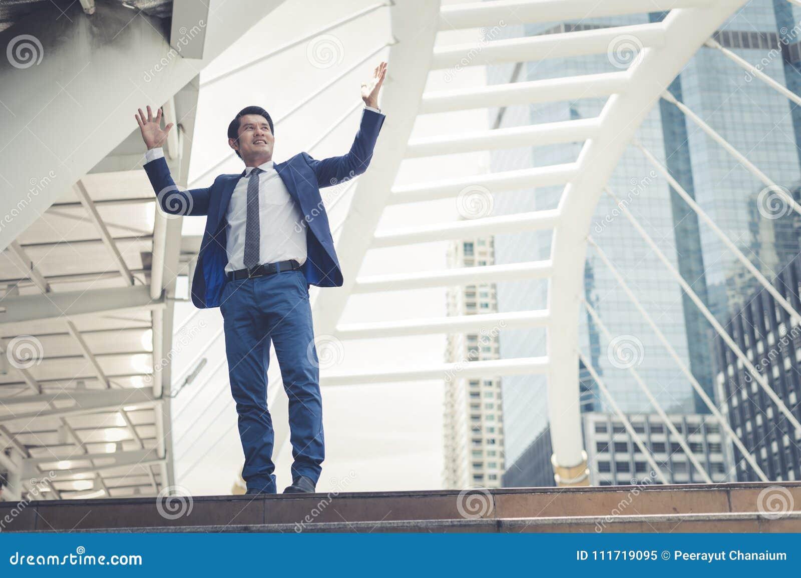 Asiatisk affärsmanställning och lyfta upp två händer till gladlynt och som firar hans lyckat i karriär och beskickning