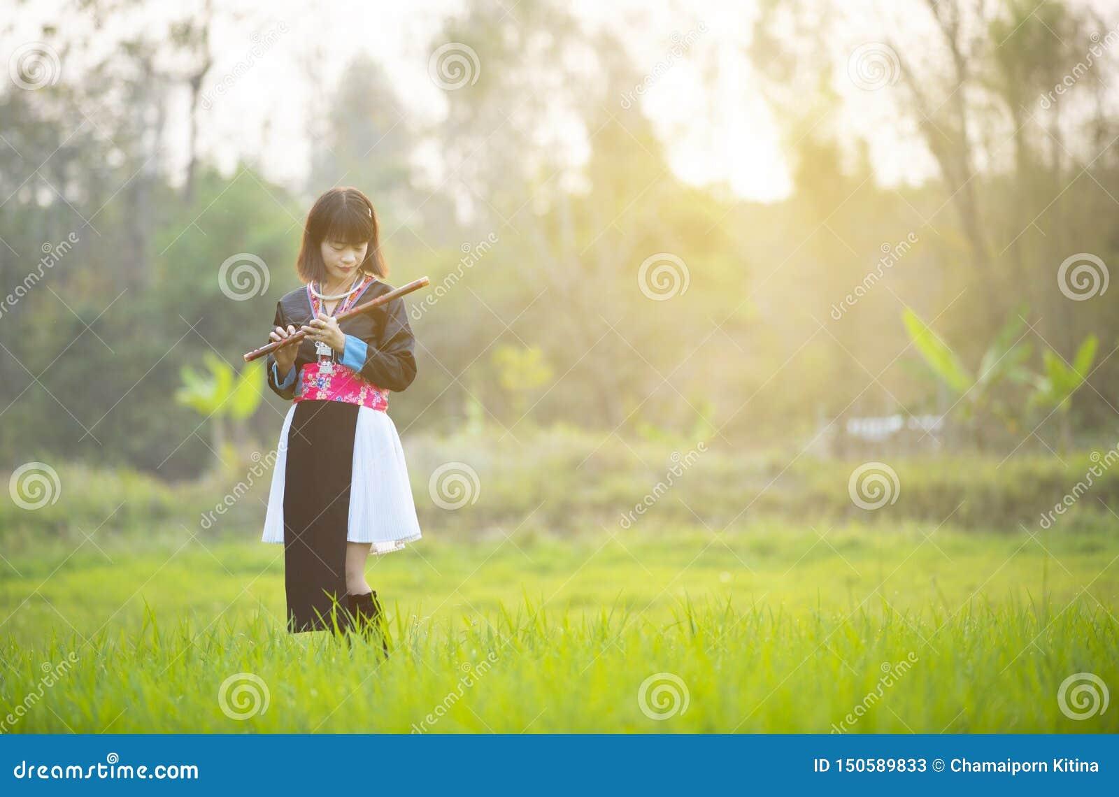 Asiatisk damflicka för stam i beställnings- flöjt för klänninghandhåll med den lyckliga framsidan som går i risfält i monsunperio