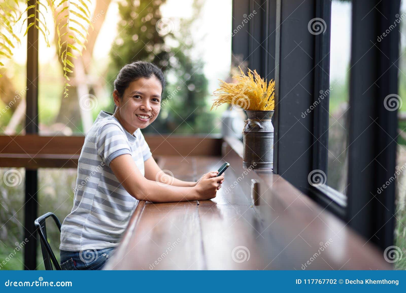 Asiatisk flicka för foto som ser kameran i coffee shop