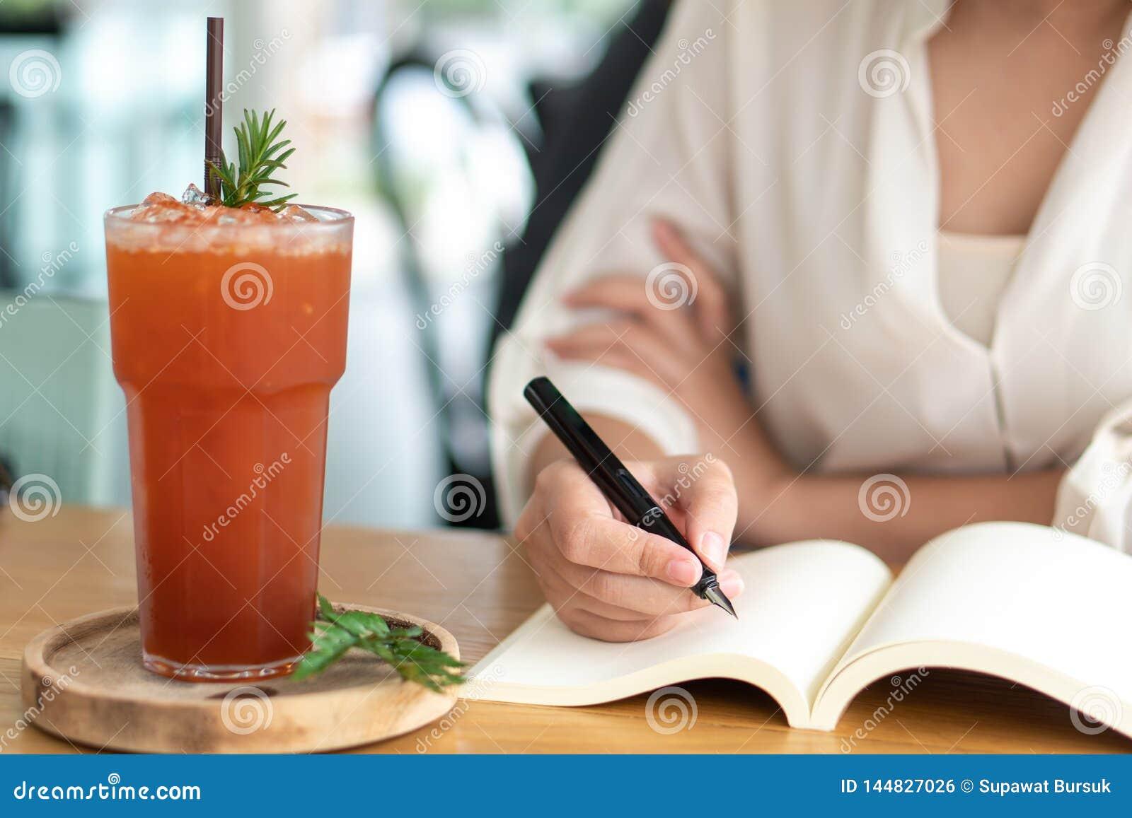 Asiatisk flicka som rymmer en svart penna som skriver in i en tom bok Dagbokhandstilber?ttelser antecknade m?ktigt Minnen p? en t