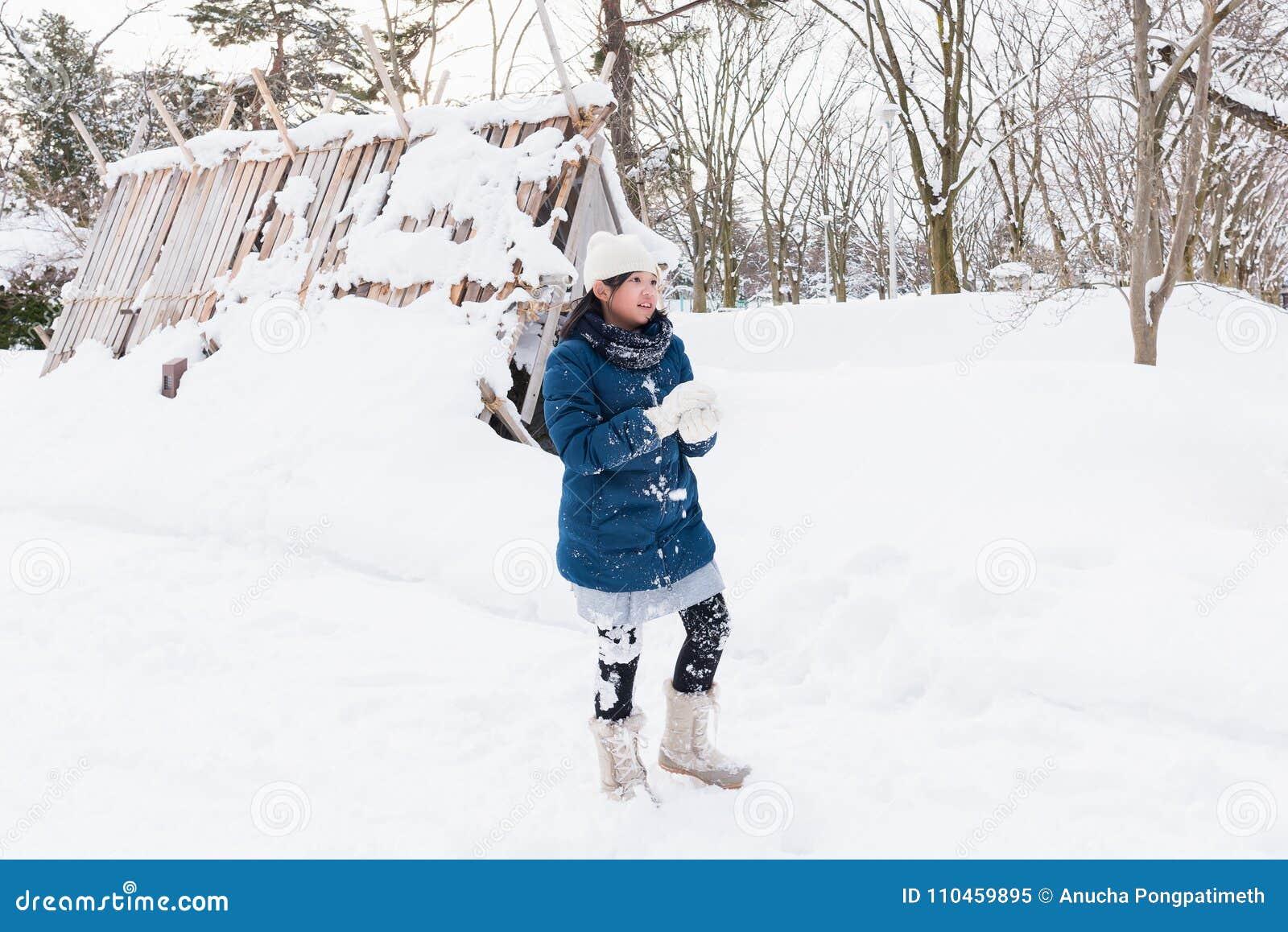 Asiatisk flicka som spelar snö