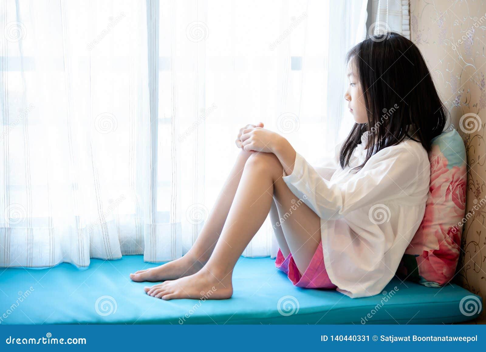 Asiatisk flicka som väntar, sitter och ser fönstret i hem