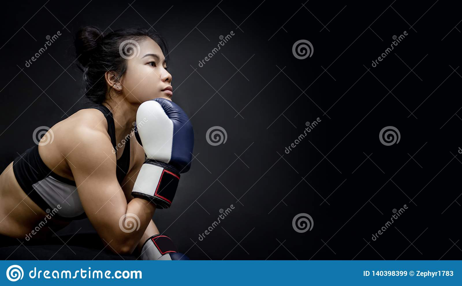Asiatisk flickaboxare som poserar med blåa boxas handskar