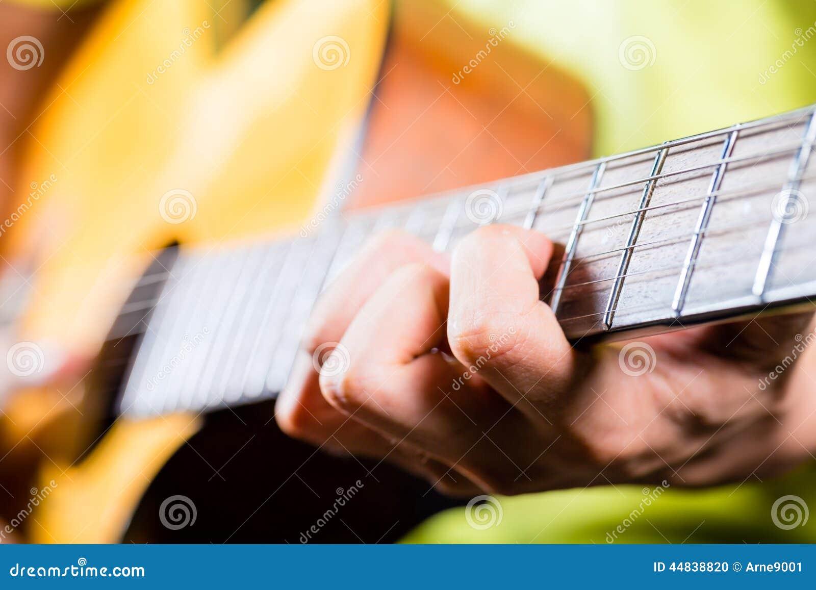 Asiatisk gitarrist som spelar musik i inspelningstudio