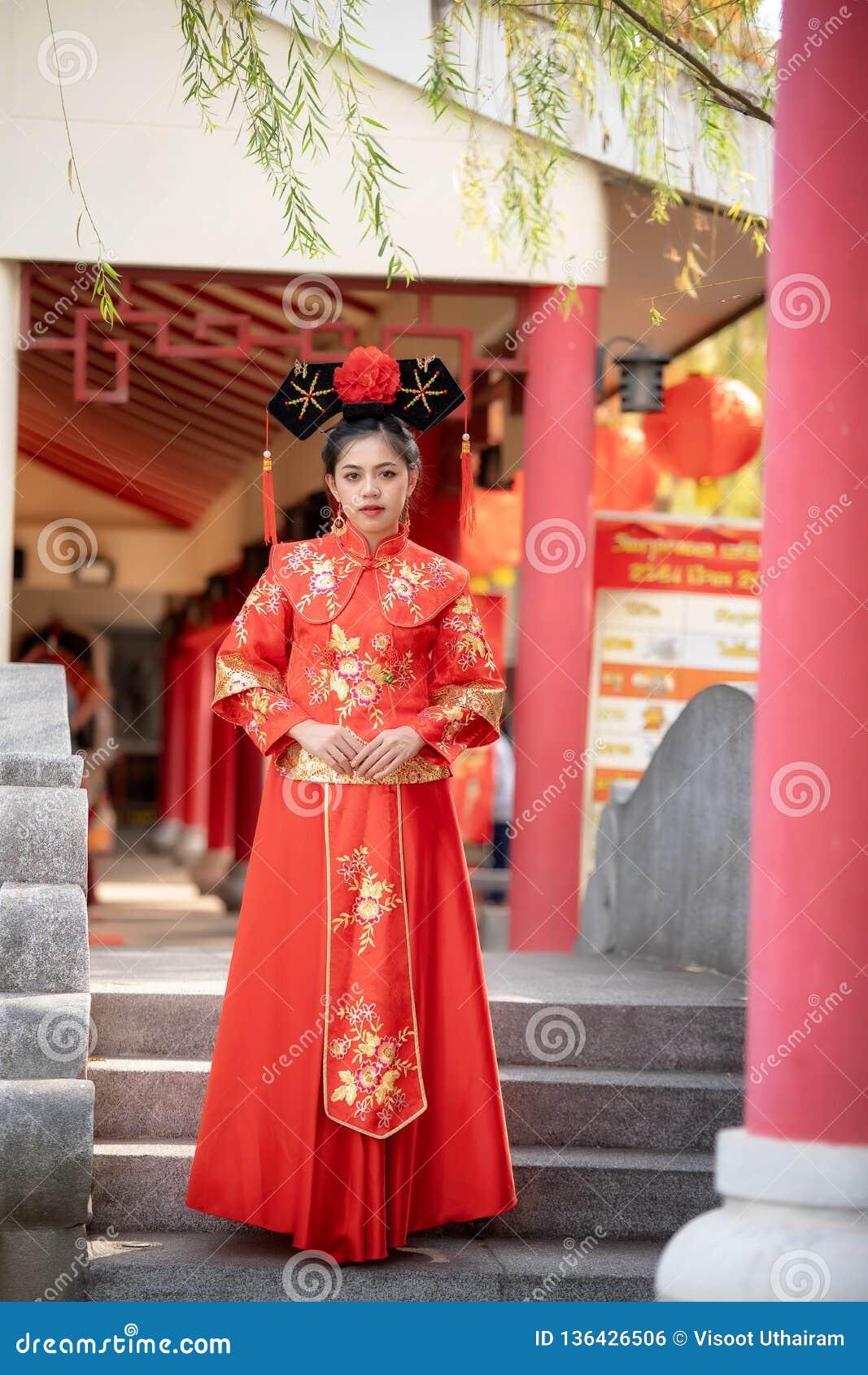 Asiatisk härlig ung kvinna som bär en traditionell kinesisk brudklänning,