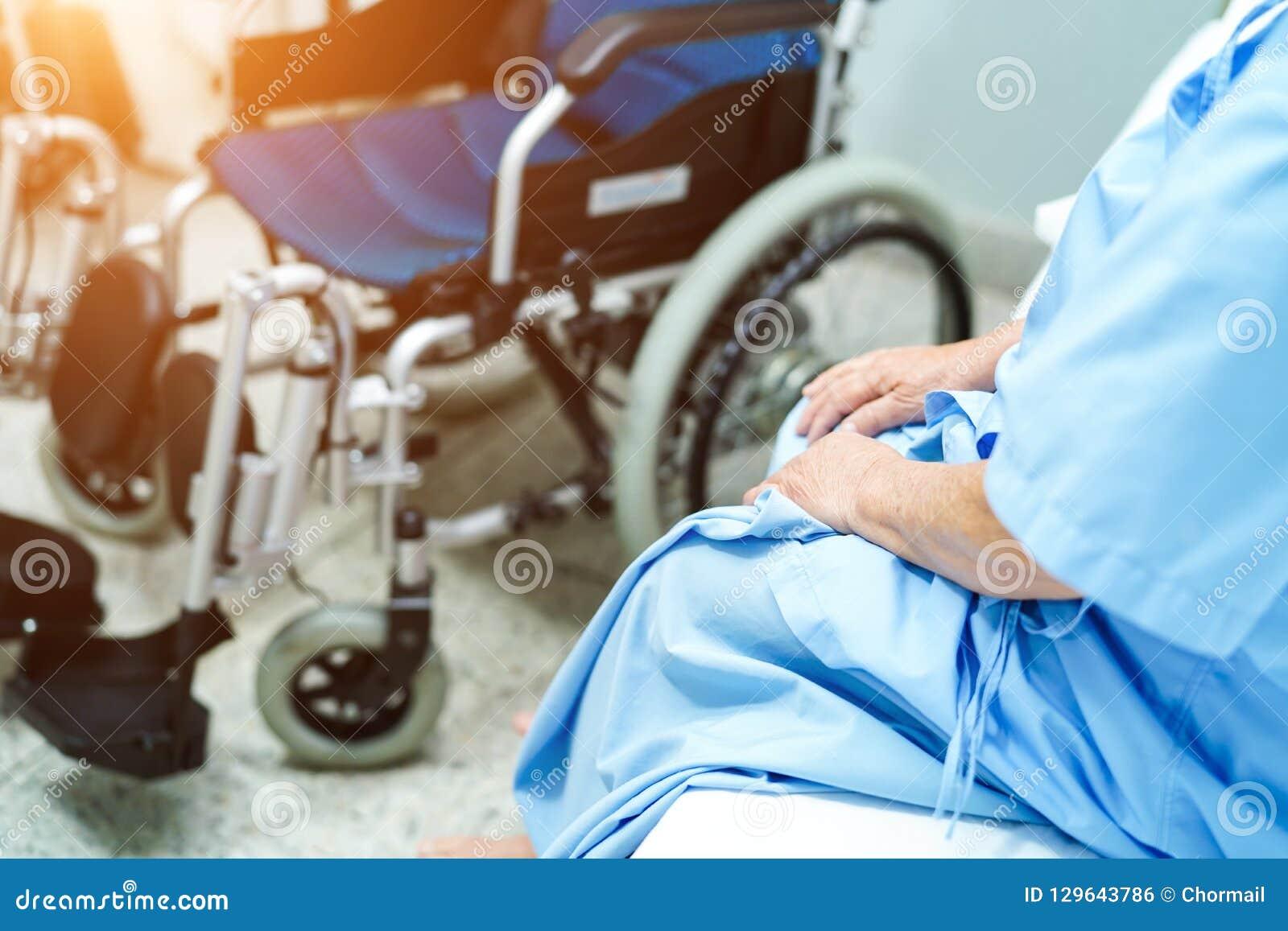 Asiatisk hög eller äldre kvinnapatient för gammal dam som sitter på säng med rullstolen, i att vårda sjukhussalen: sunt starkt me